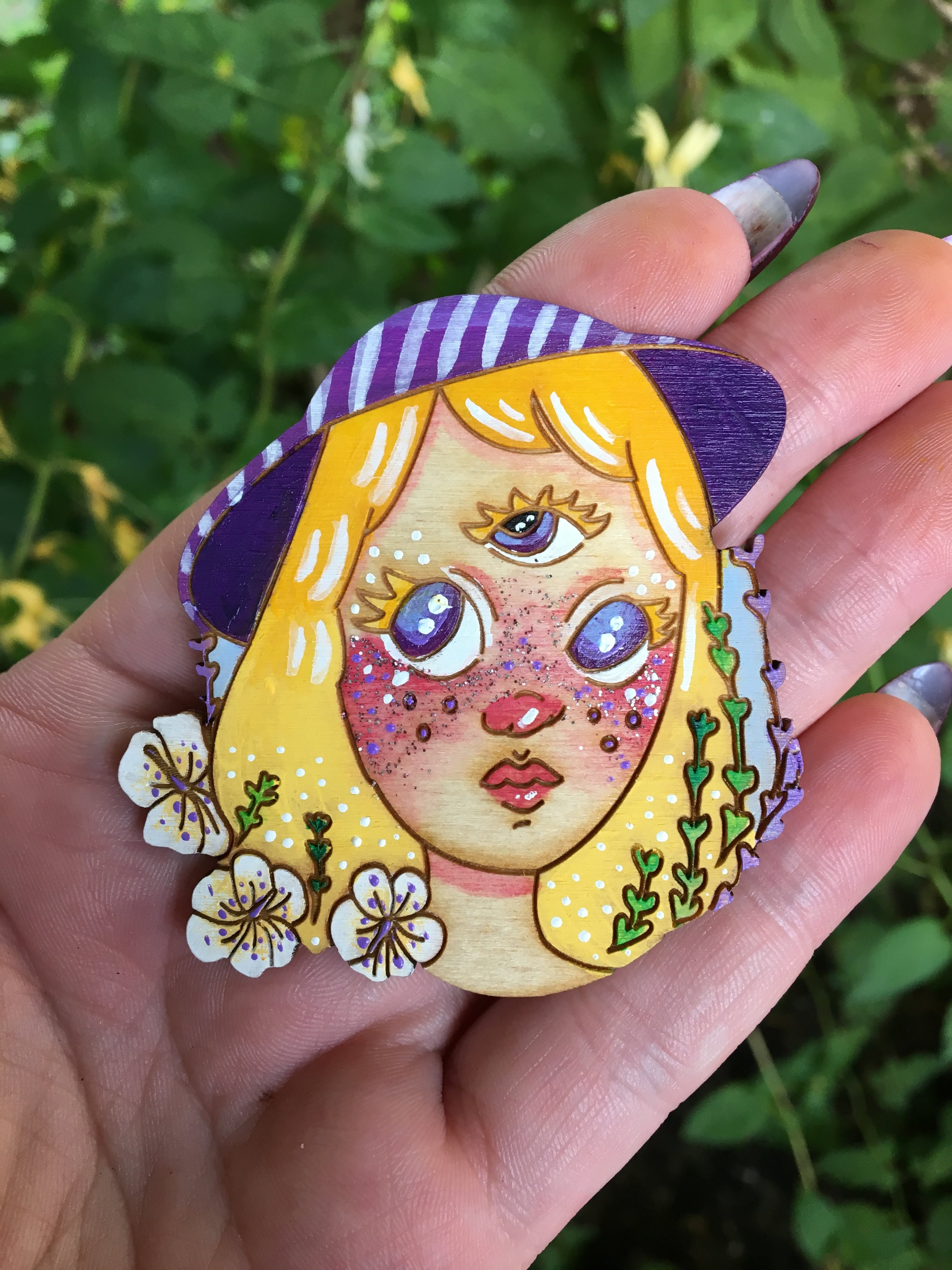 Image of a wooden brooch with a blonde, three-eyed person and flowers painted on the brooch