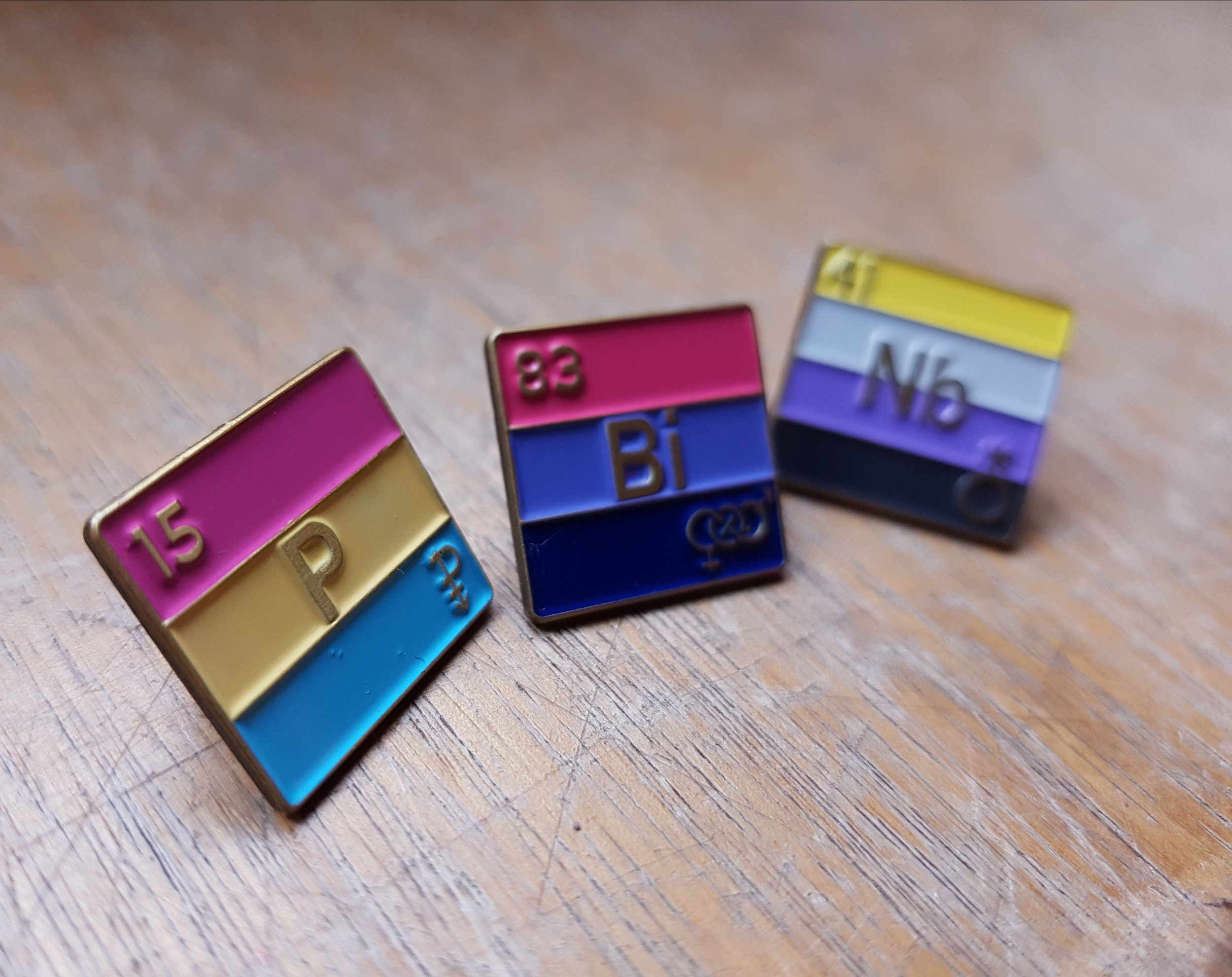 Image of three periodic element pins; left pin is pansexual flag, middle pin is bisexual flag, and right pin is nonbinary flag