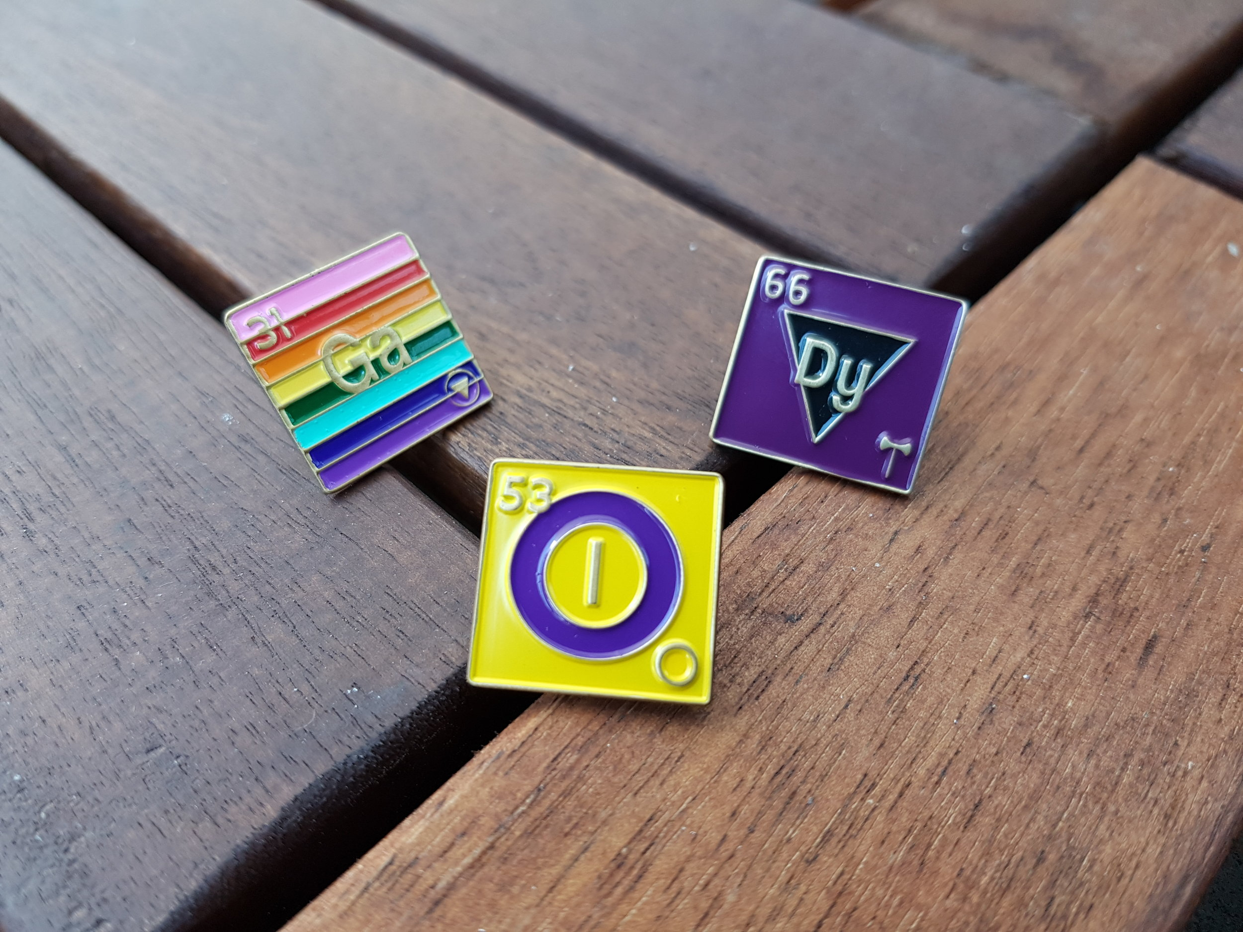 Image of three periodic element pins; left pin is gay pride flag, middle pin is intersex pride flag, right pin is dyke lesbian pride flag