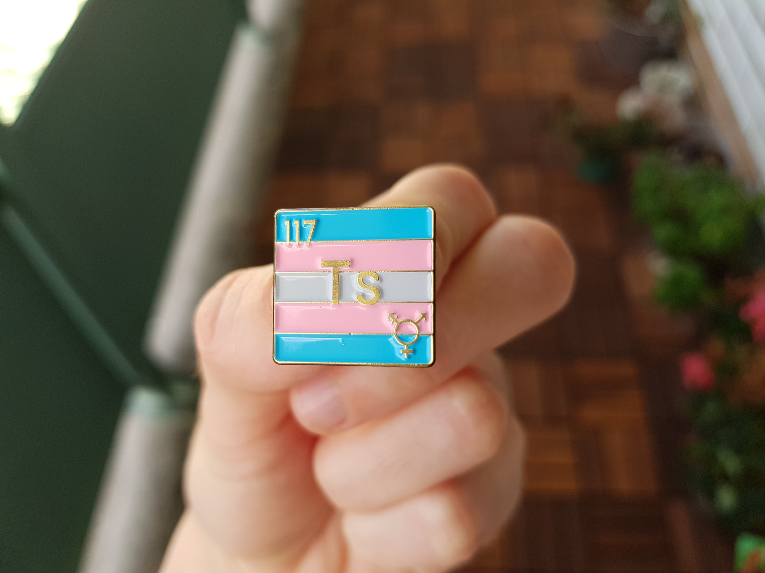 Image of hand holding a periodic element pin with the transgender pride flag