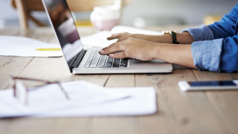 Freiberufler mit Notebook und Unterlagen am Arbeitstisch
