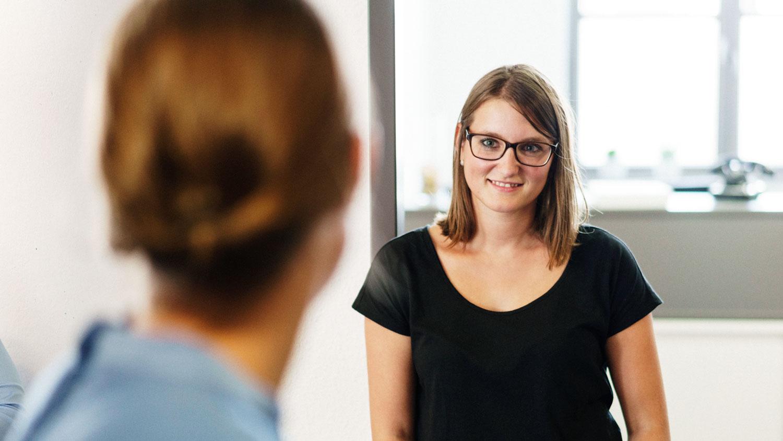 Steuerberaterin Rachel Dreher und junge Frau unterhalten sich freundlich
