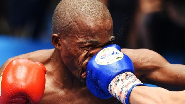Moruti Mthalane is punched by Masayuki Kuroda during their IBF flyweight title bout in Tokyo. (Photo by CHARLY TRIBALLEAU / AFP) Source:AFP