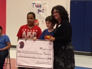 Students presenting their donation from their profits to their charity.