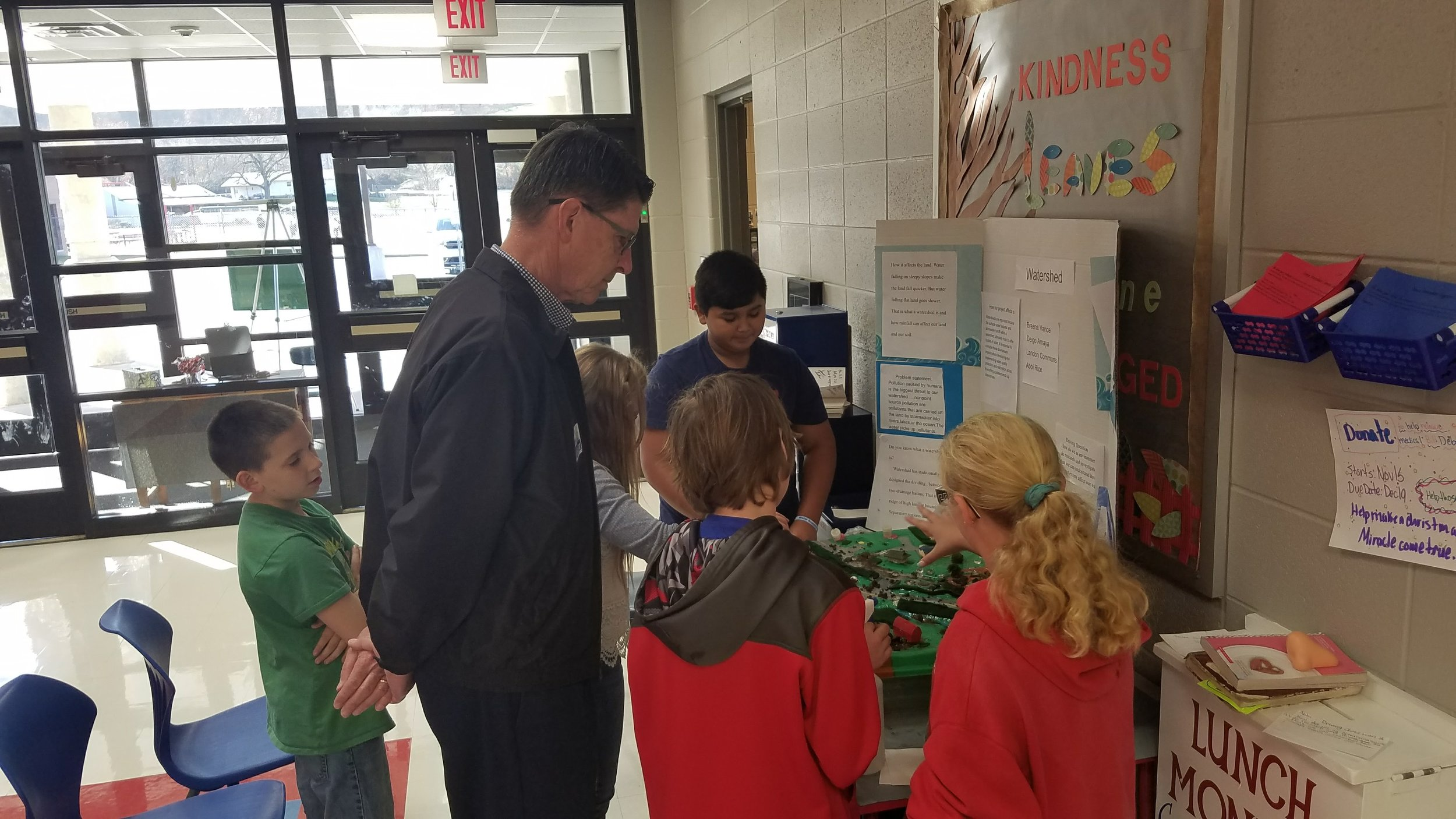 Student Environmentalists discuss pollution in a watershed with a community partner and fourth grade students.