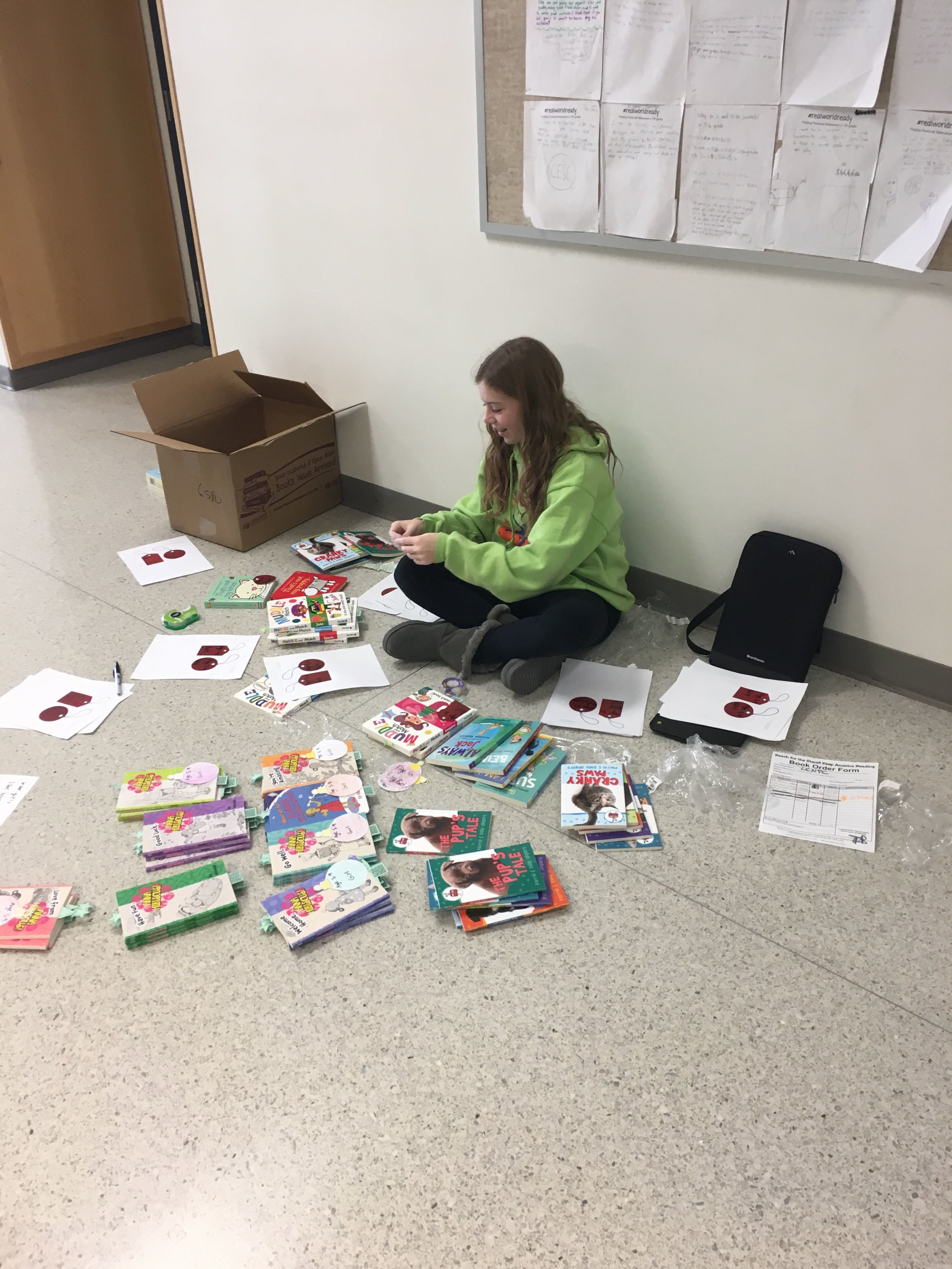 Student putting labels on packets of books.
