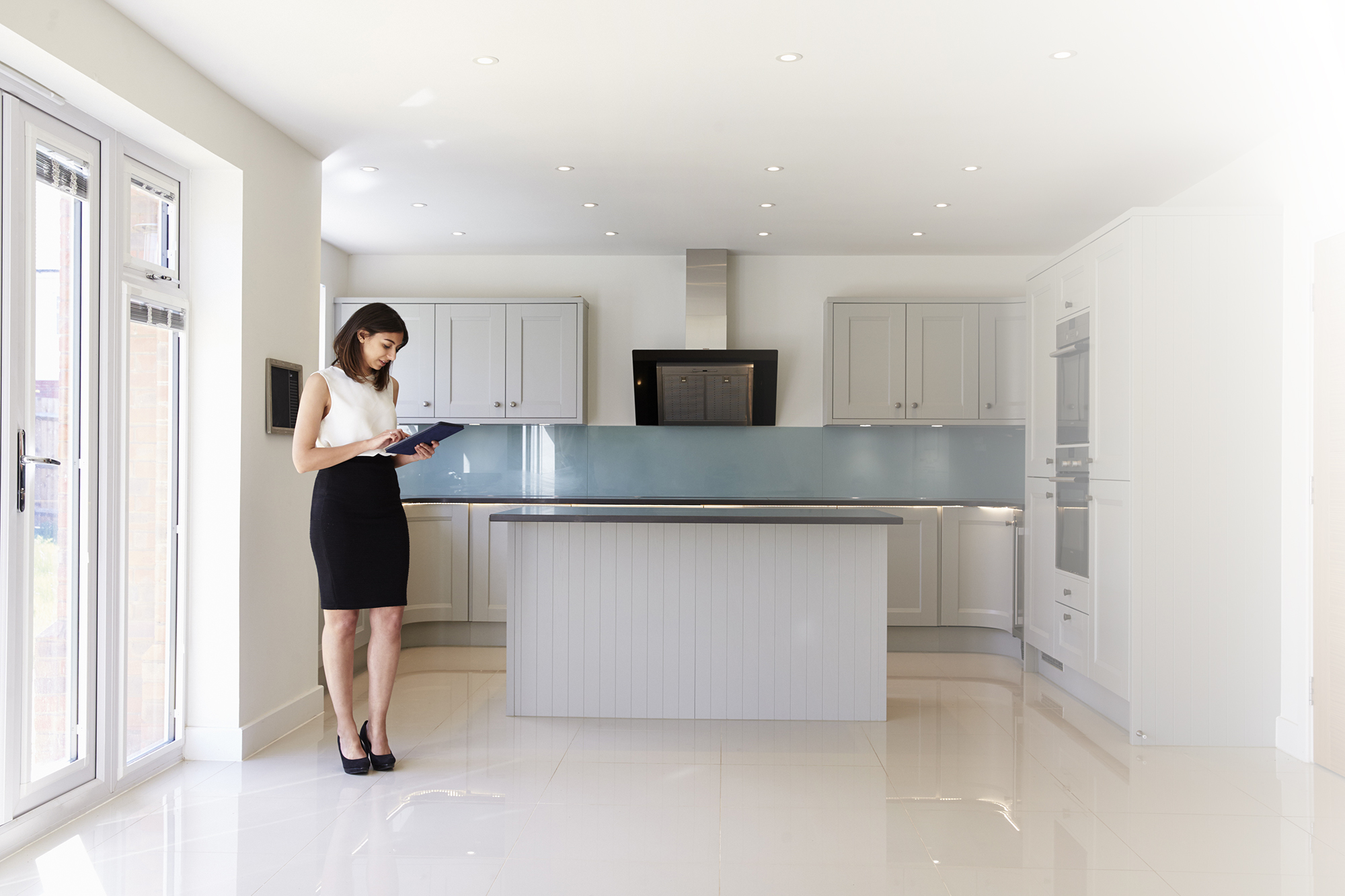female-realtor-in-kitchen-carrying-out-valuation-P5ZSZWL.jpg