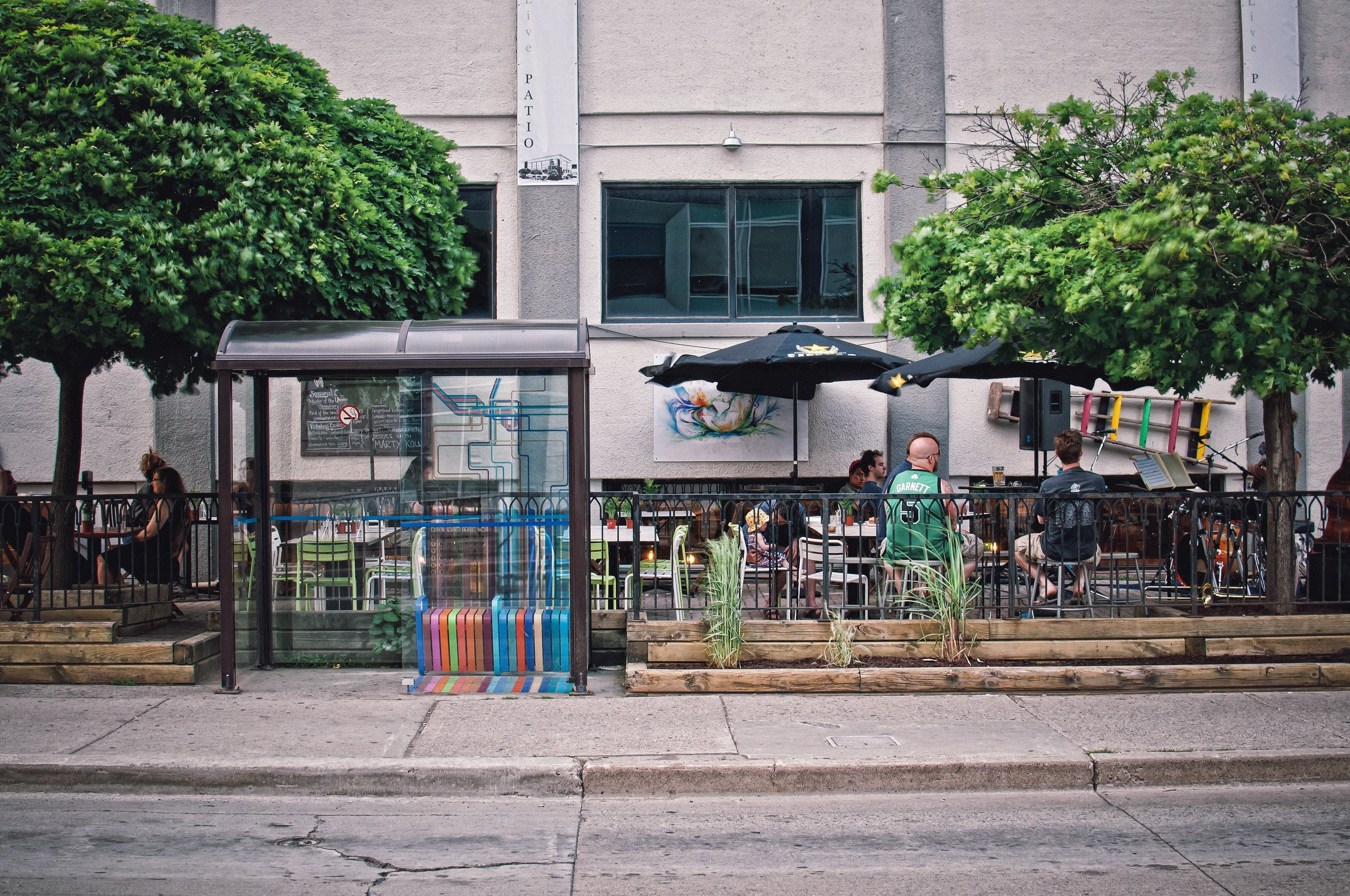 APK Live outdoor patio, with bus stop art installation by Ryan Ollson. Photo Credit:  Scott Webb