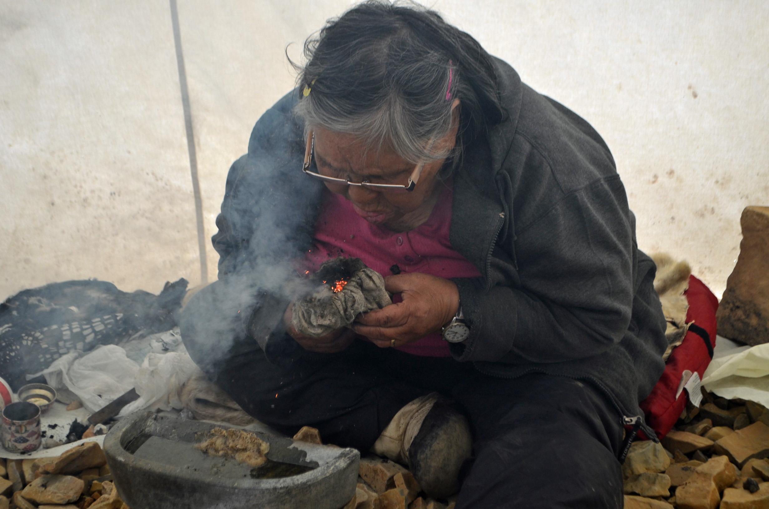 Allissa Kamingmalik demonstrates how to start a qulliq lamp from flint stones.jpg
