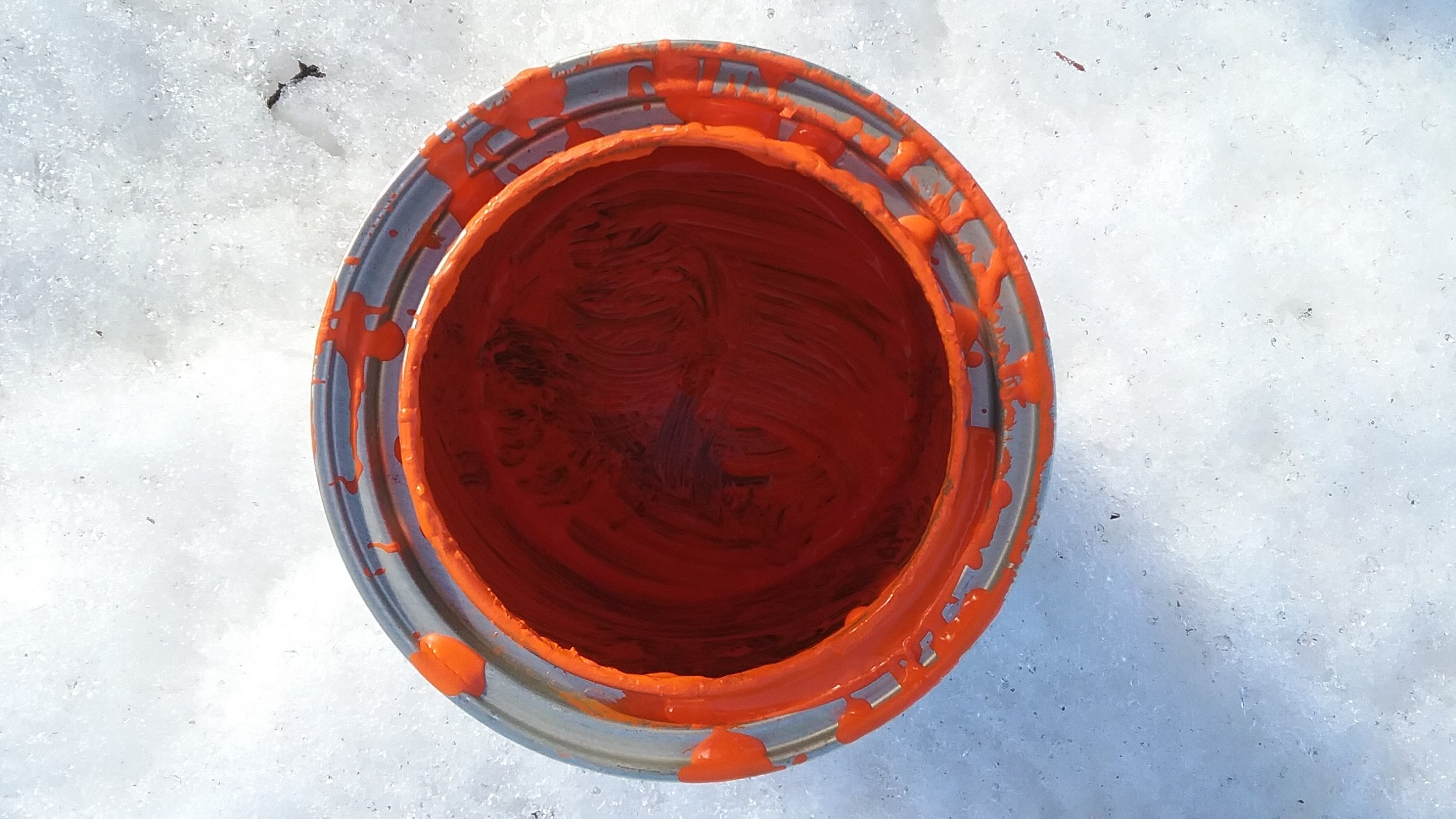 An empty pail of Pantone 021-ish paint for the pallets. In the snow, because it was still winter when we started this project.