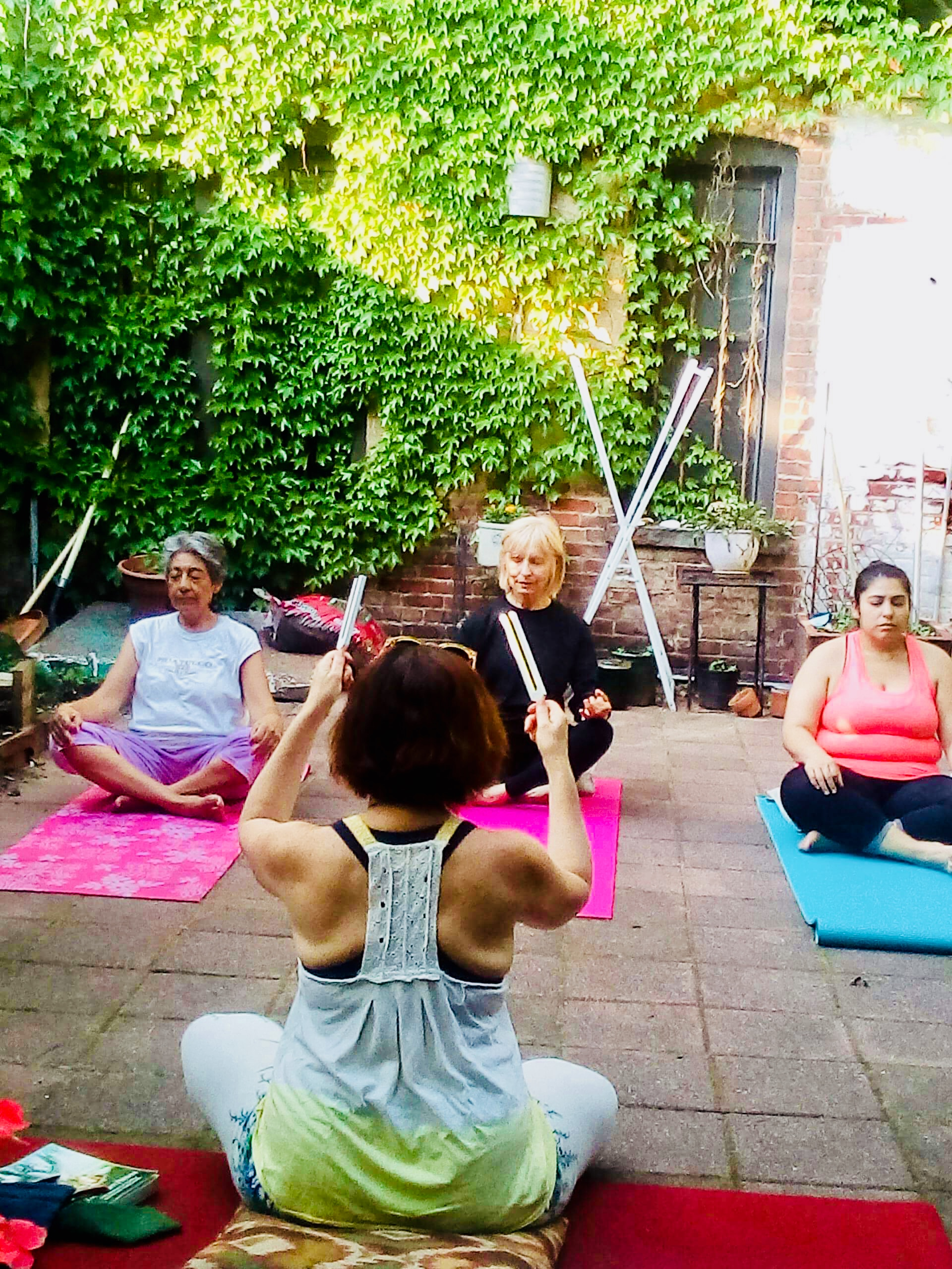 Teaching a yoga class to a small group in the backyard of my Sunset Park brownstone.
