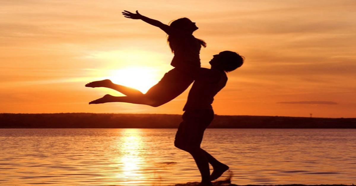 sunset silouhette man lifiting woman.png
