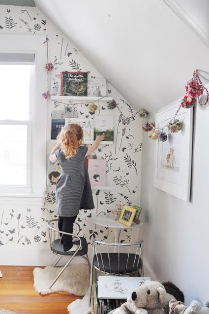 girl reaching for books in room with wall stencil.jpg