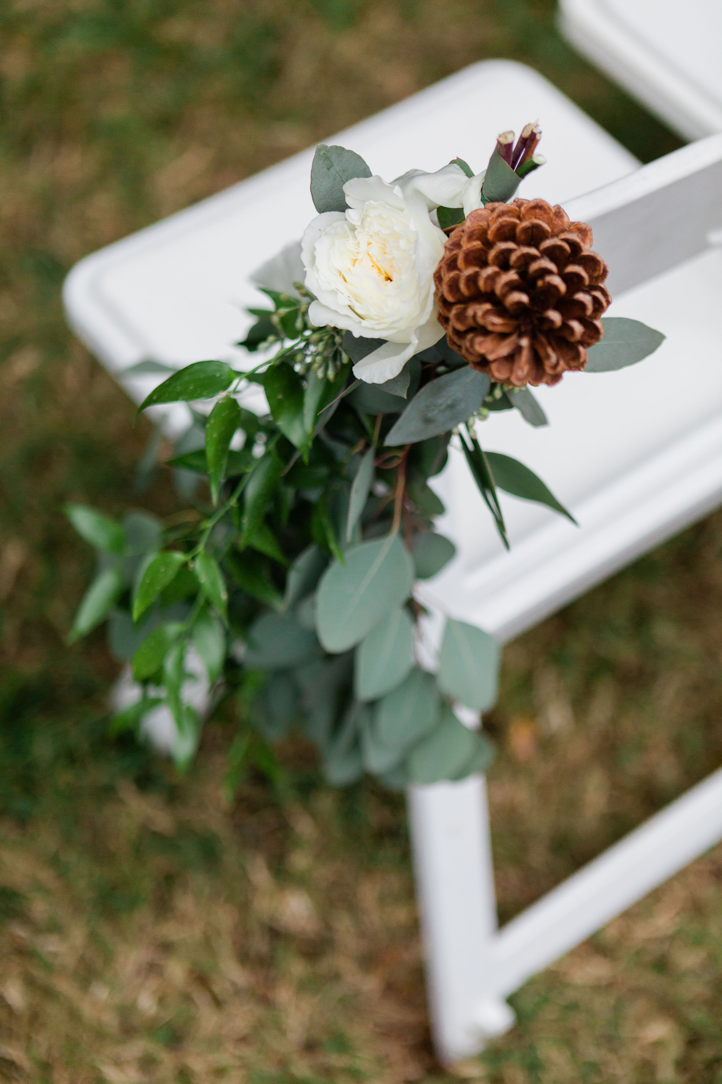 Gorgeous burgundy and white roses came together to create Rebecca's cascading bouquet. The bride and groom exchanged vows with a lush, green backdrop, layered with soft linens, while rosemary and sugar pine cones detailed the aisle decor and dinner table centerpieces. #floraldesign #weddingflorals #weddingflowers #virginiawedding #virginiabride #virginiaflorist