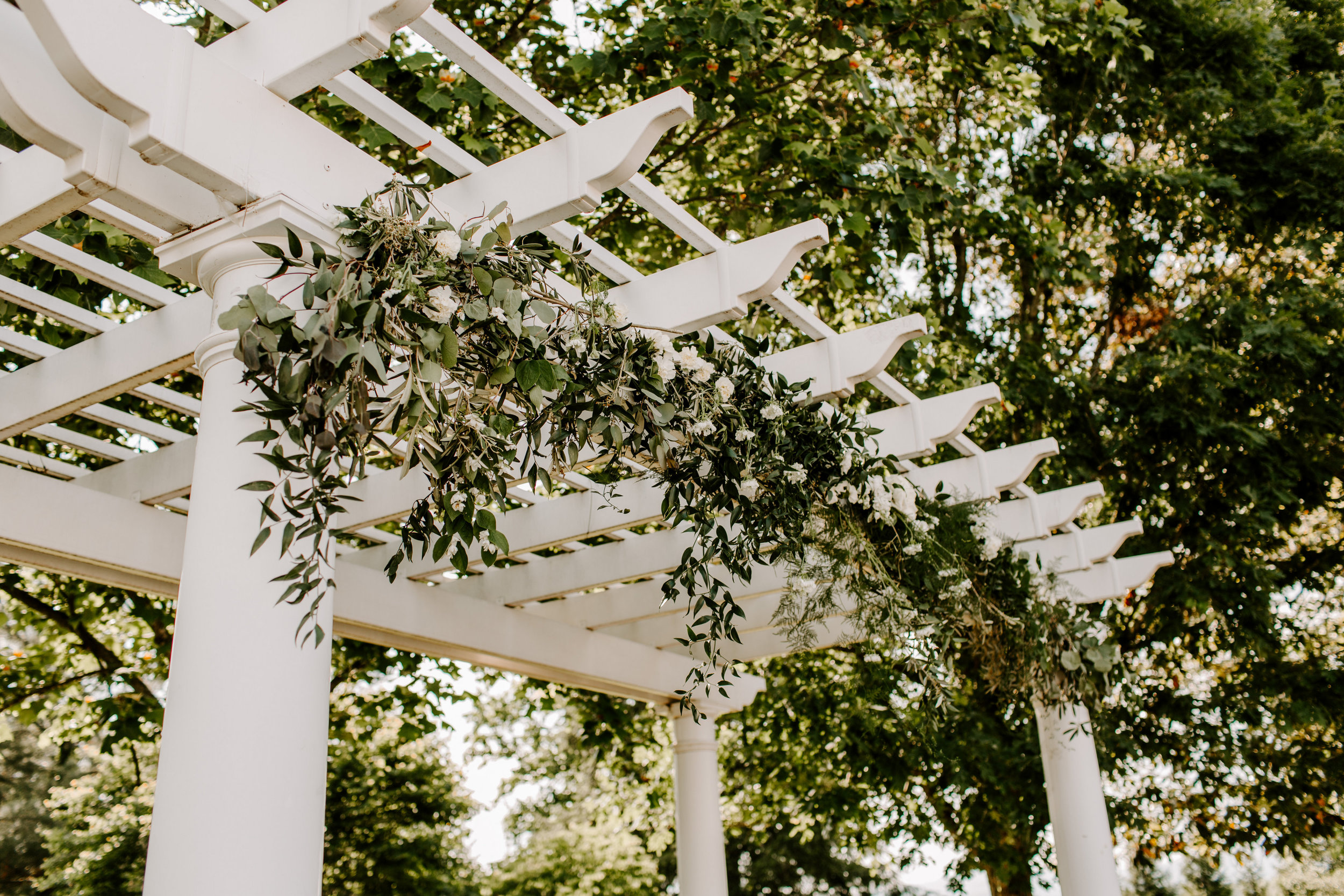 This sweet couple kept their wedding day floral aesthetic simple in color, but rich in texture. Salmon toned florals paired perfectly with the bridesmaids' gowns, while the bride carried a bouquet with white roses. The ceremony took place under a gazebo clad with greenery - the theme continued into the reception, with ferns and eucalyptus all around.