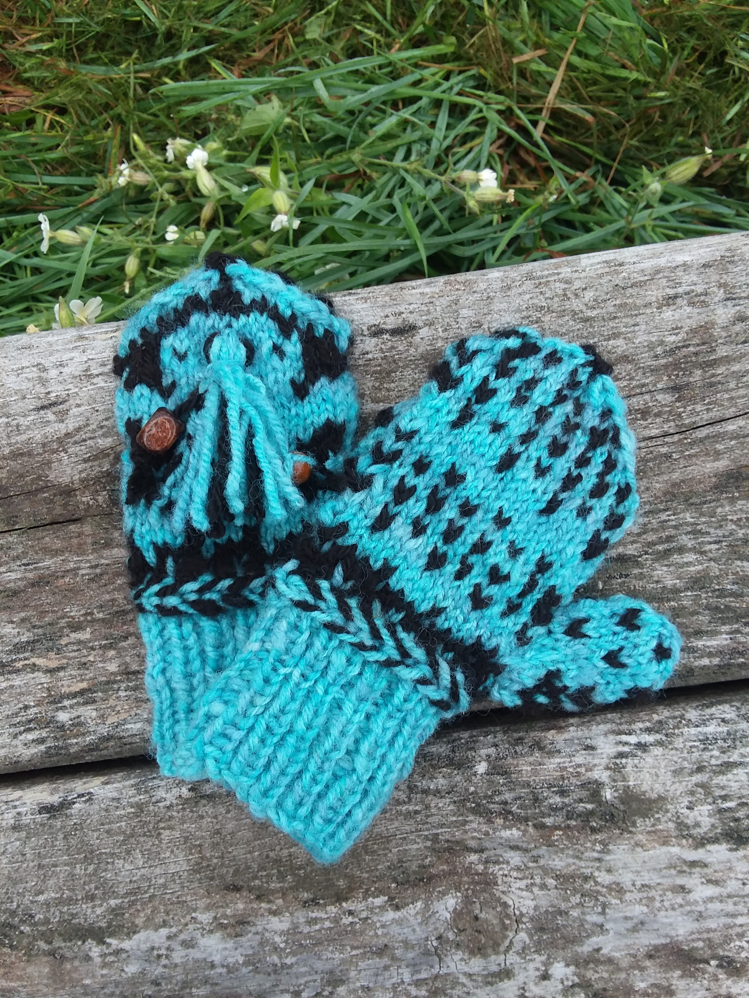Front and backside views of my 4T mittens. Made from handspun, hand dyed wool and handspun natural black alpaca yarns.