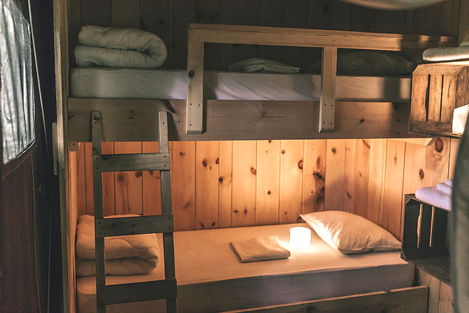 The Bunk room is a small private room within the glamping tent. It has a twin bunk bed inside and shelves along the wall for your personal items. Enjoy a quiet little space of your own or share with a friend.