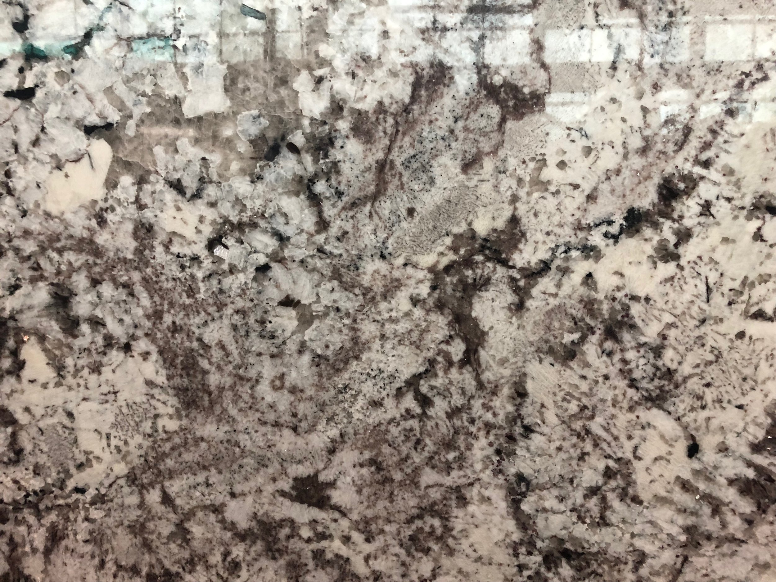 ATLAS WHITE - Quarried: IndiaMaterial Type: GraniteDescription: white and cream base coloring with breaks of brown, grey and blacks in random patterning throughout.