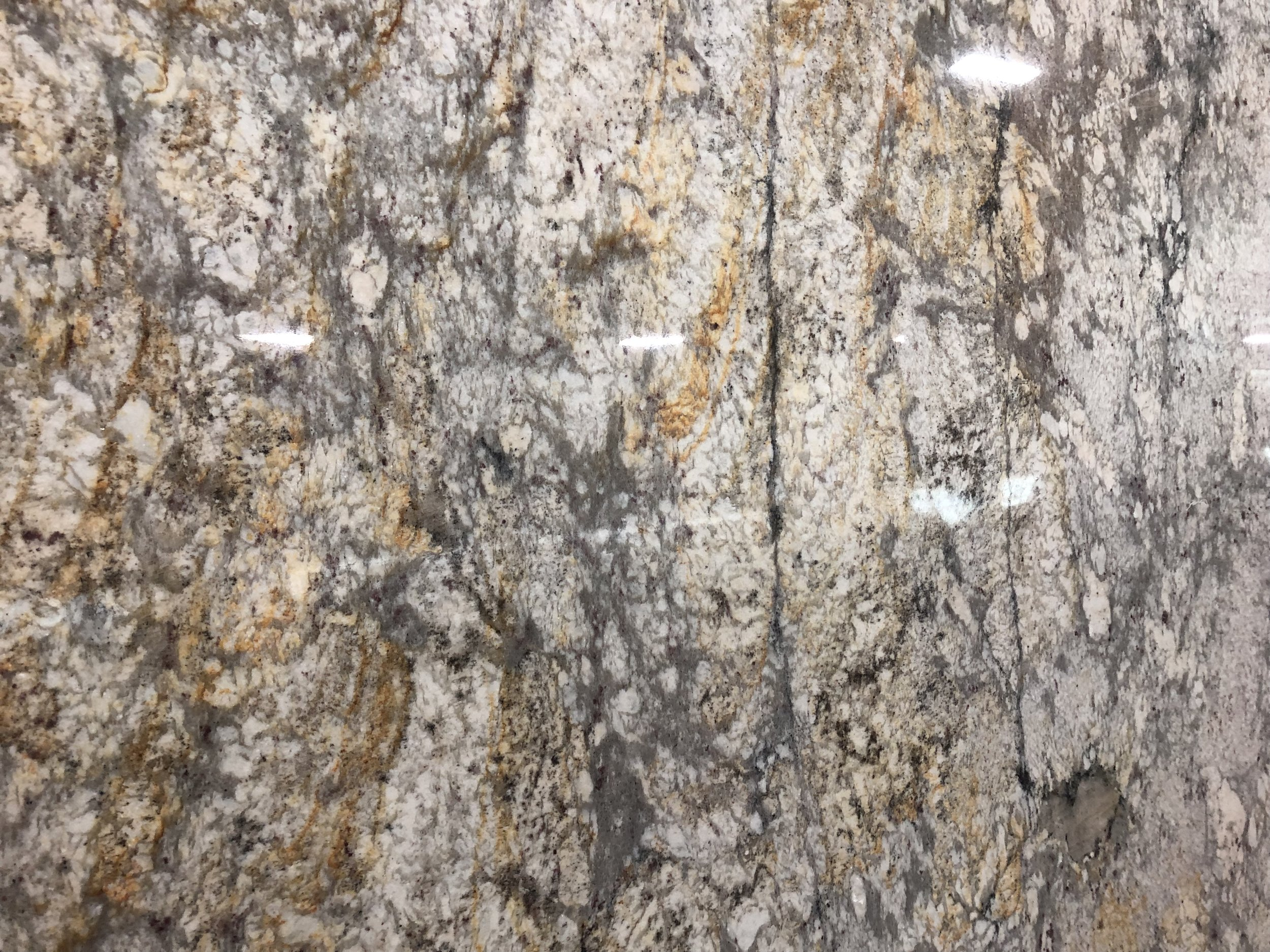 Sienna gray - Quarried: IndiaMaterial Type: GraniteDescription: grey and white base color with heavy deposits of yellows and dark grey veining.