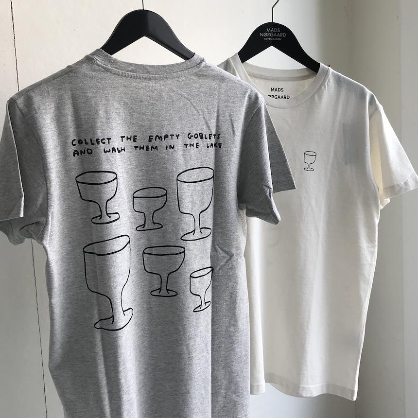 Heartland T-shirt - Årets officielle Heartland T-shirt er skabt af kunstneren David Shrigley, der står bag gigaværket SWAN-THING på dette års festival.Det humoristiske print er trykt på et design af Mads Nørgaard, der sammen med Heartland har skabt T-shirten, selvfølgelig i genanvendt bomuldsblend.Den kommer i tre udgaver: sort, ecru og gråmelange, koster 250 kr. og kan købes på festivalen og efterfølgende hos Mads Nørgaard og på madsnorgaard.dk