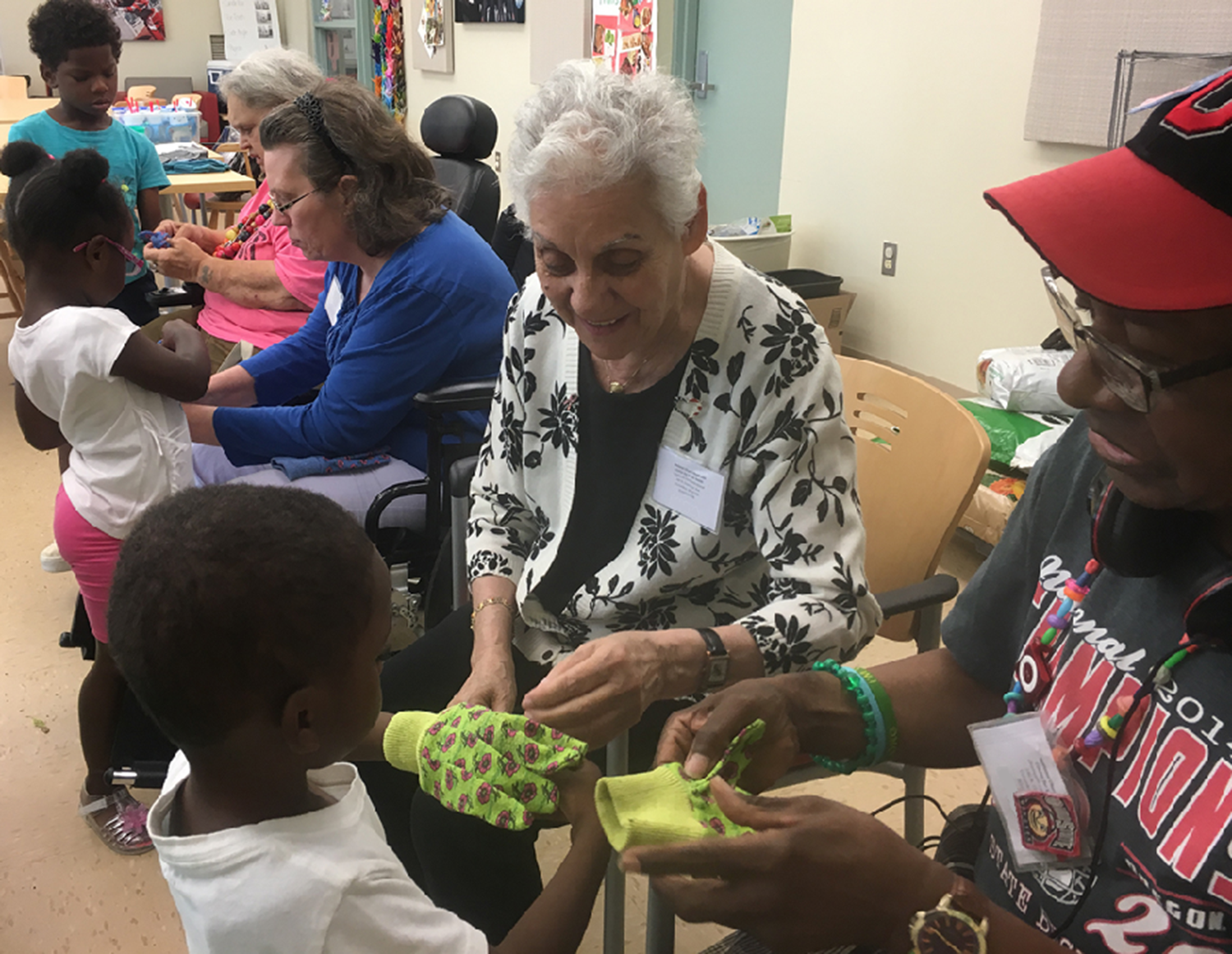 Adults placing gardening gloves on the preschool children's hands.