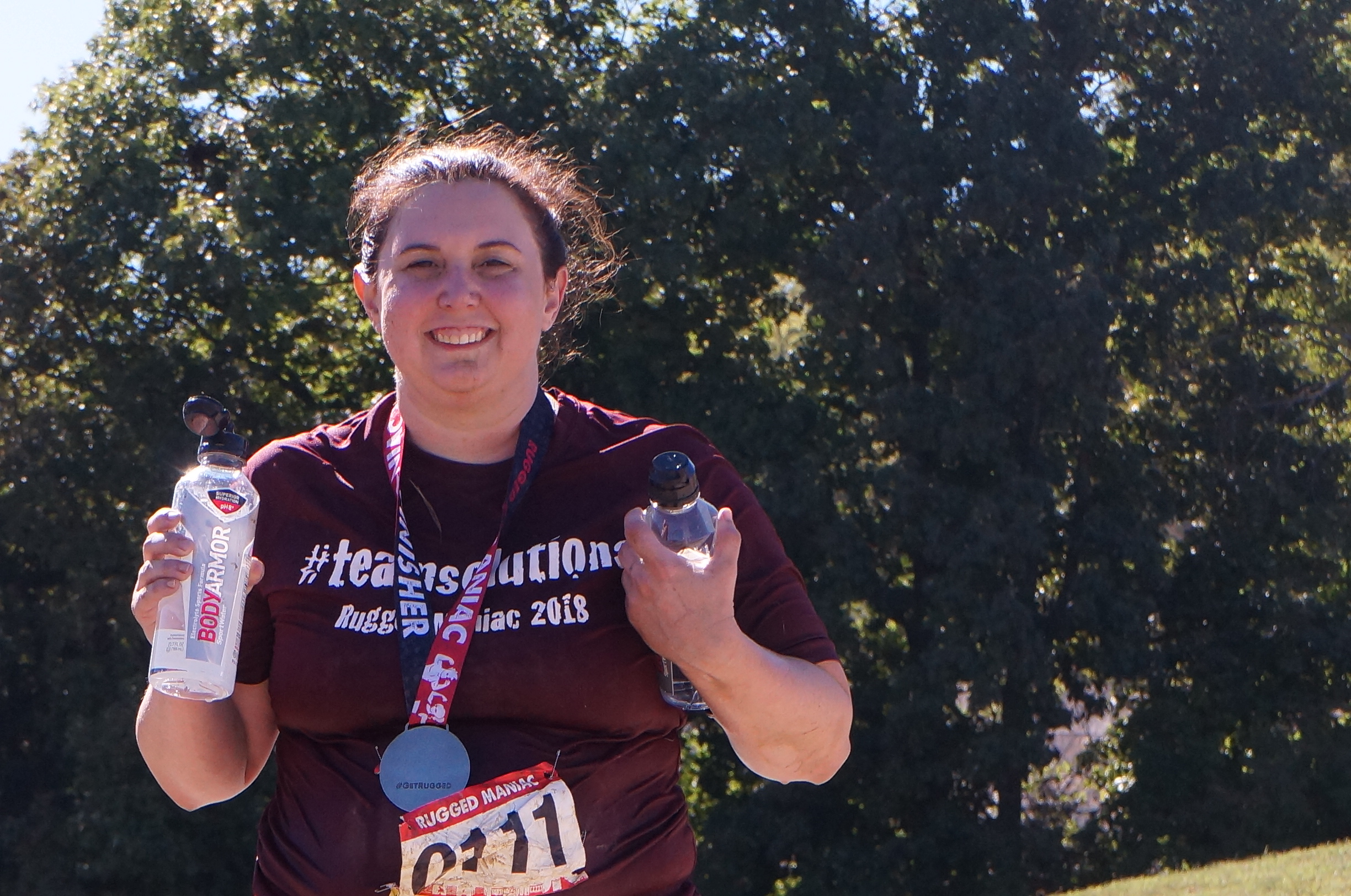 Carisa showing her finisher's medal with a big proud smile.