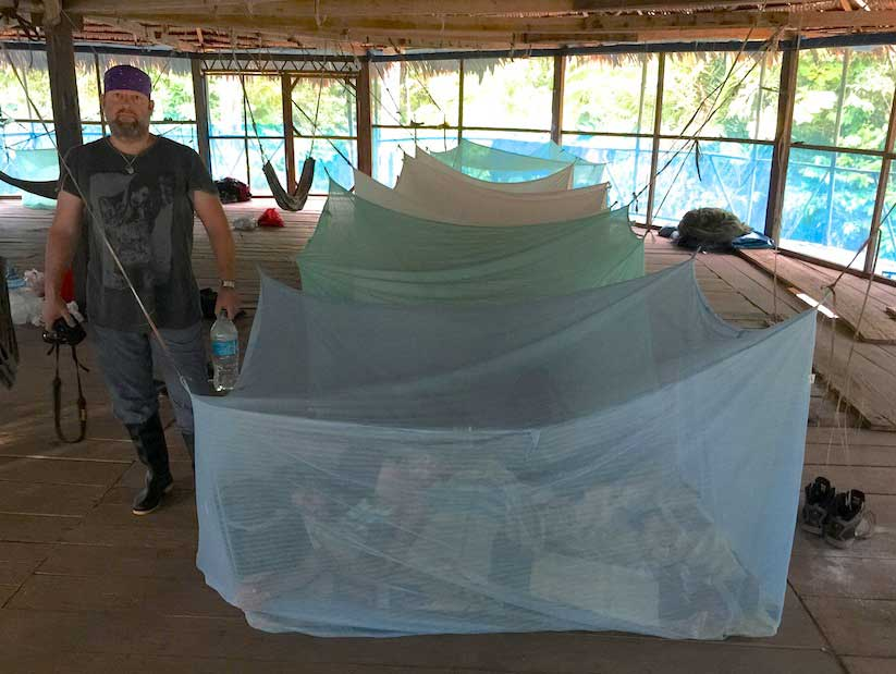 """Peruvian Amazon Loreto, Peru – Along the banks of a small tributary. Jake stands in front of our second layer of defense against the busy Amazonian mosquitoes in Mosquito Net Row in the """"Kiva"""" building. The first layer is the mosquito screen enrobing the entire """"Kiva"""" hut, the second of course our """"night chambers"""" where we took refuge from the ones who got into the Kiva.  Sleeping on a wood floor with little padding was easy after tracking through mud and jungle all day, we would return, eat and sleep."""