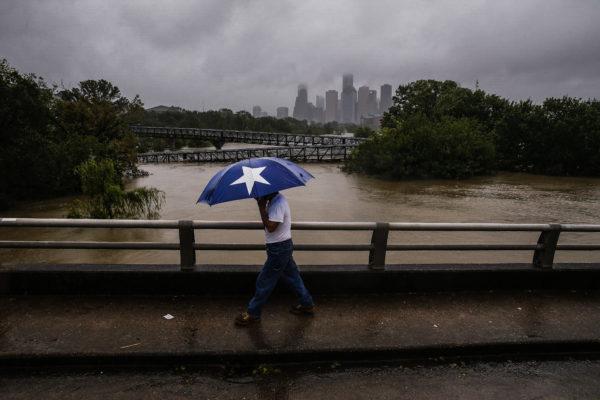 Armando Bustamante walks along Studemont Street over Buffalo Bayou as flood waters from Hurricane Harvey flow toward downtown Houston on Tuesday, Aug. 29, 2017. Michael Ciago/Houston Chronicle