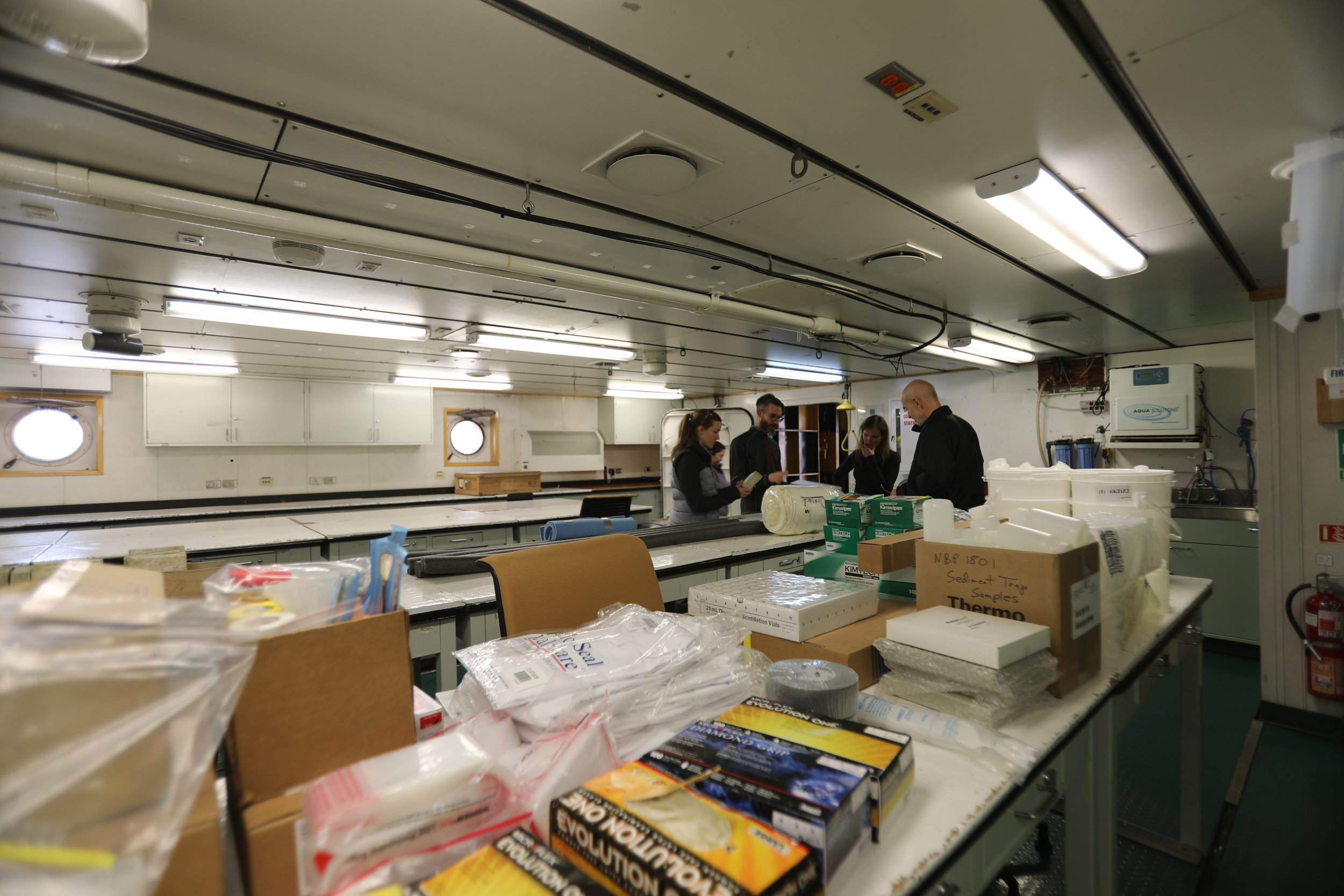 THOR team members (l to r)- Rebecca Totten Minzoni, Alastair Graham, Rachel Clark, Rob Larter- sort through and distribute core processing supplies in the core processing lab. All drawers and cabinets have dog-locks to ensure they do not open during passage through rough seas.