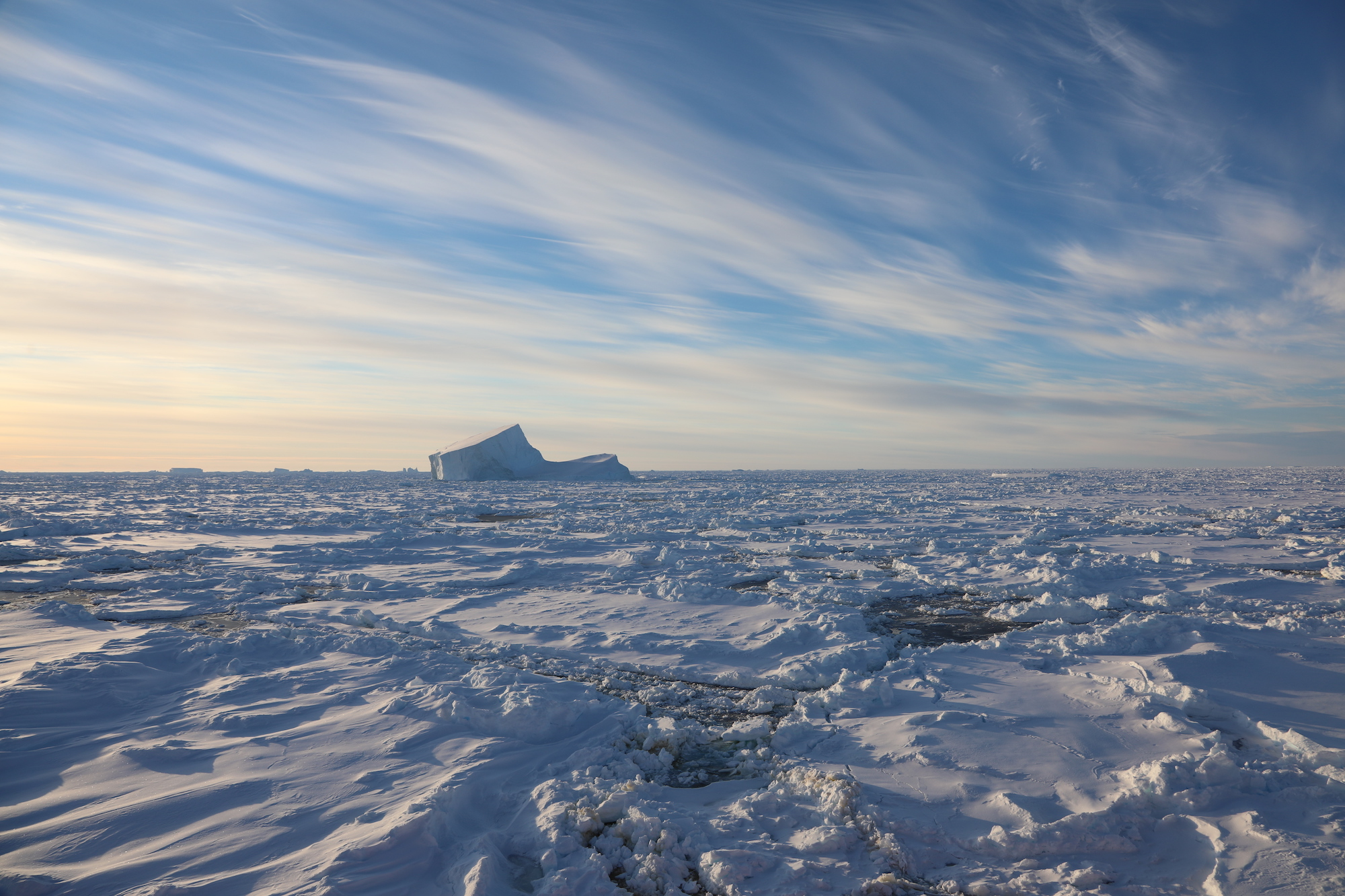 Sea ice (foreground) with an iceberg protruding and more bergs on the horizon.