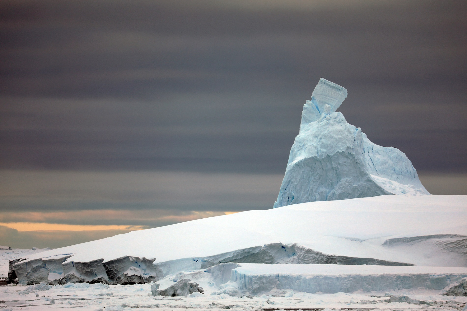 An  iceberg  peaked by a precariously perched pinnacle.