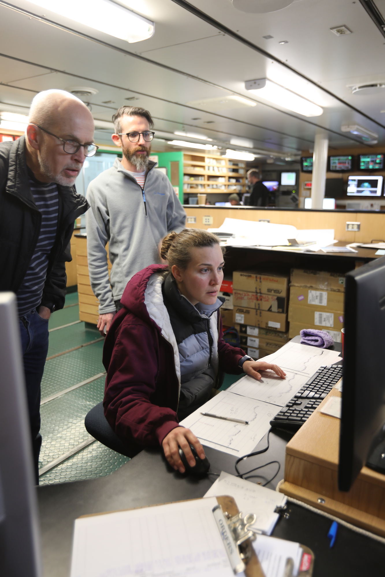 (Left to right) Rob Larter, Ali Graham and Becky Minzoni compare the Knudsen sub-profile images with new bathymetry gathered after arriving at Thwaites glacier.