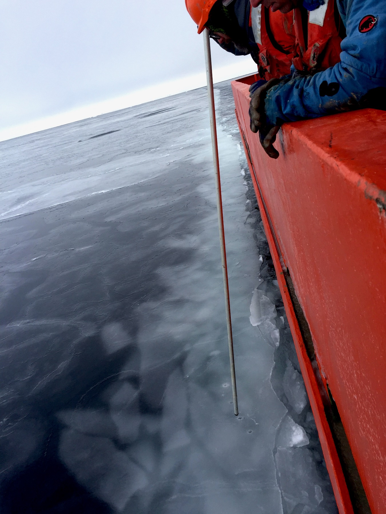 Joey Patterson tests the strength of the sea ice prior to deploying the Kasten corer.