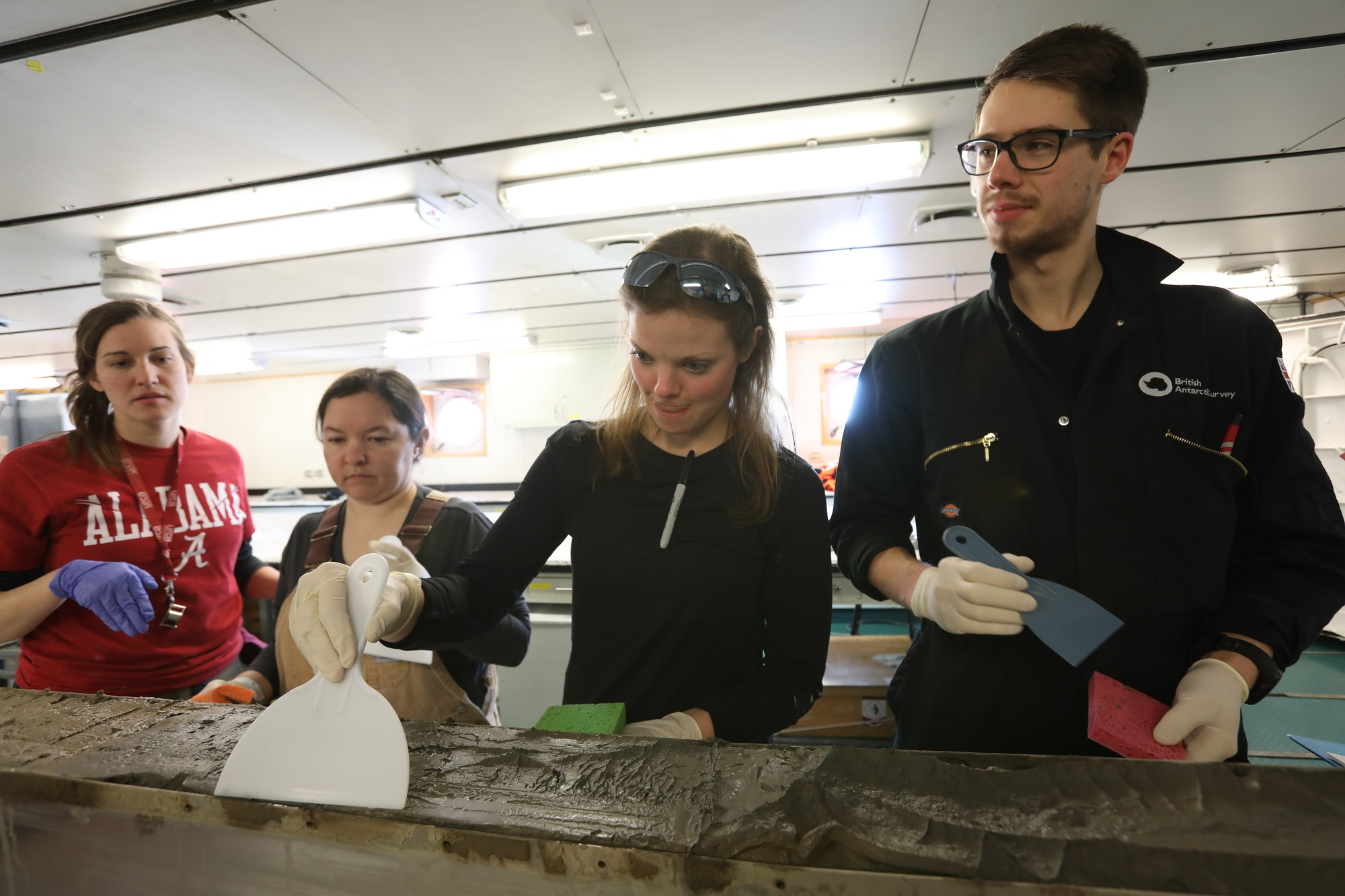 The Kasten core surface is scraped smooth by (right to left) Ph.D. students James Kirkham, Rachel Clark and Victoria Fitzgerald with drywall mud scraper. Becky Minzoni explains the process.