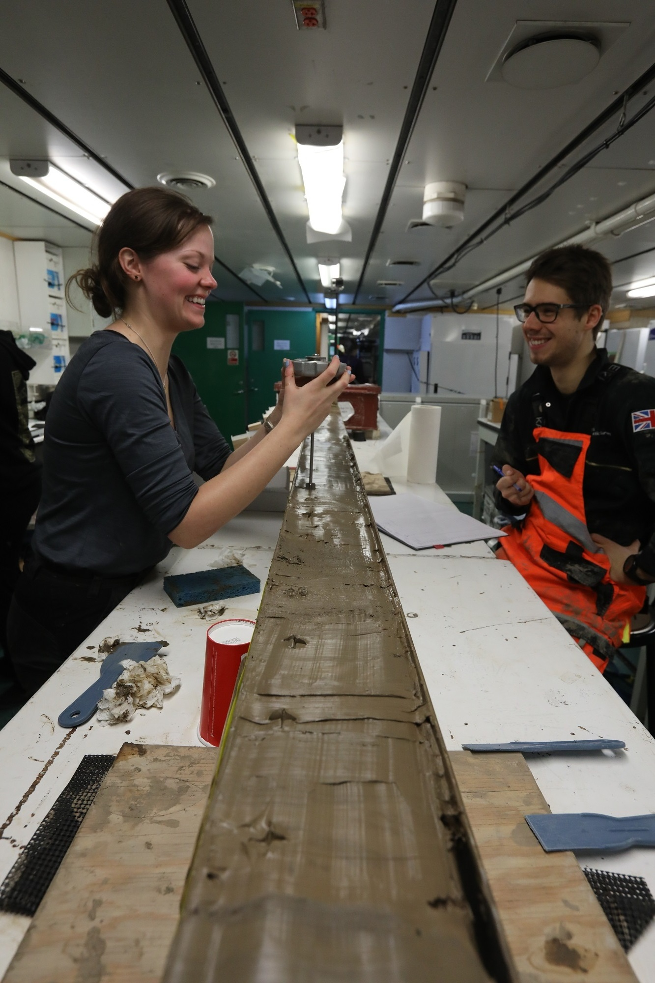 Ph.D. students Rachel Clark and James Kirkham use a Torvane to measure the strength of the mud. Measurements are taken from the top few millimeters of the core surface every 10 centimeters.