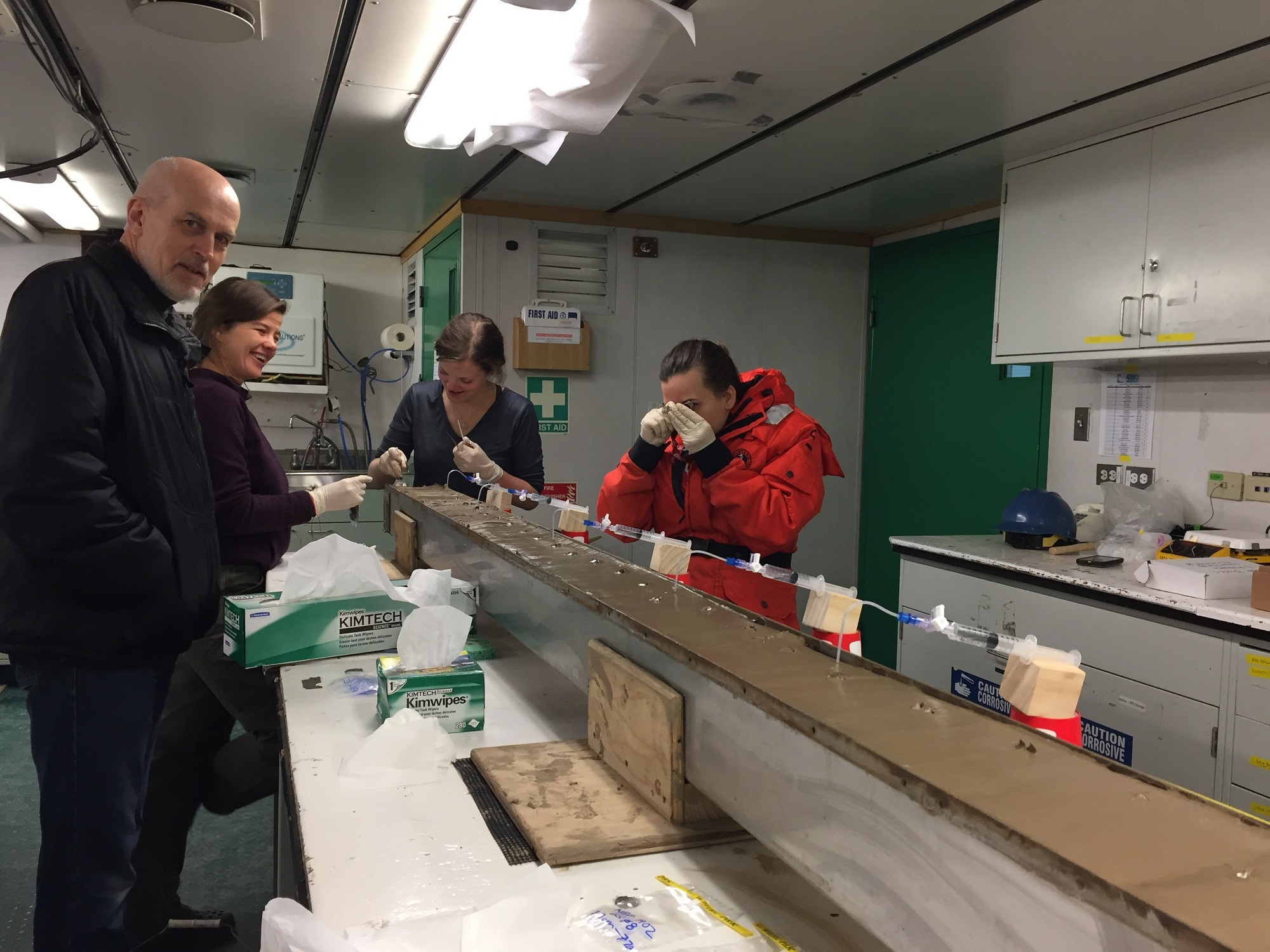 Becky Minzoni looks at the sediments with a hand lens as she describes the grainsize of the core. Also pictured (l to R) THOR PI Rob Larter, Author Elizabeth Rush, and Ph.D. student Rachel Clark.