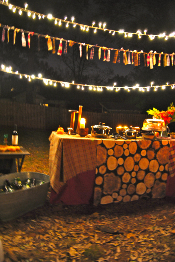 The glow of the lights, candles and fire pit and the cozy plaid table covering and garland make this outdoor party insanely inviting.