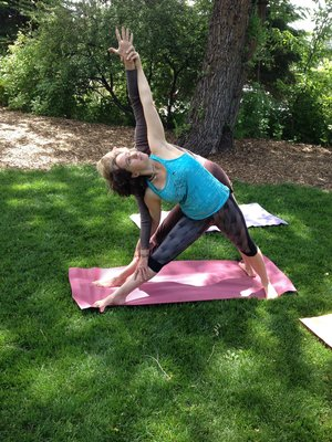 Yoga instructor and guest in a side stretch