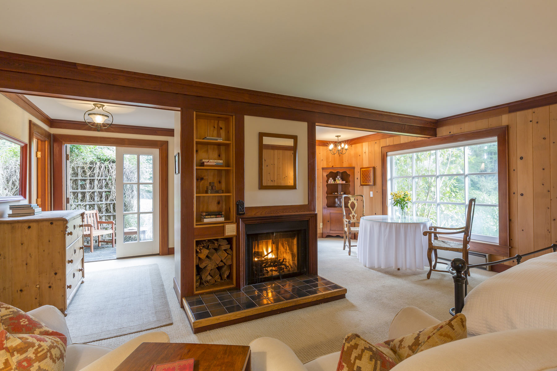 The Pinewood room with pine paneling, fireplace, sitting area, and French doors leading out to the garden.