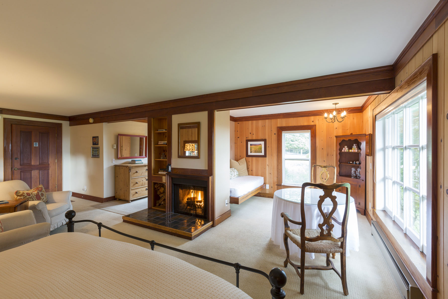 The Pinewood room with fireplace, seating area, and iron king bed