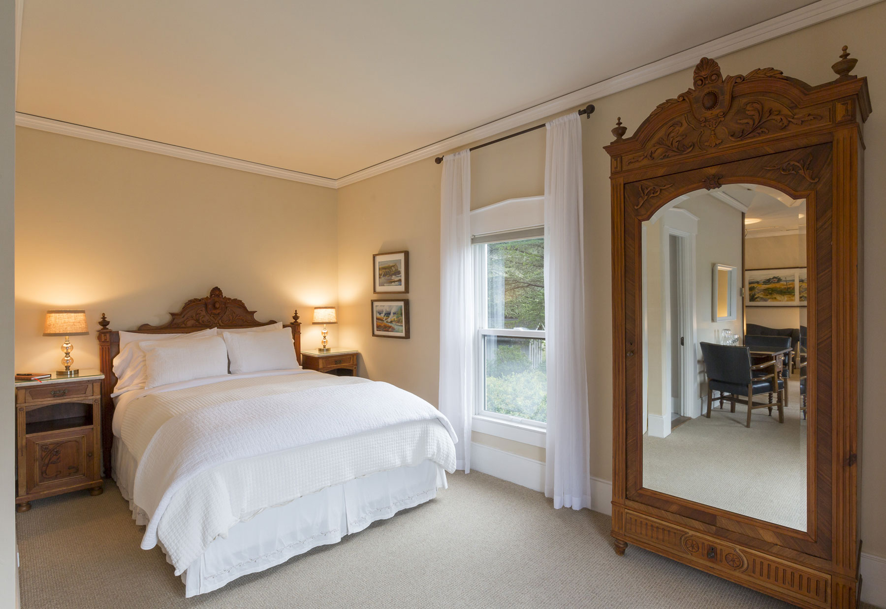 Bayview Suite with queen featherbed, antique furnishings, and view windows.