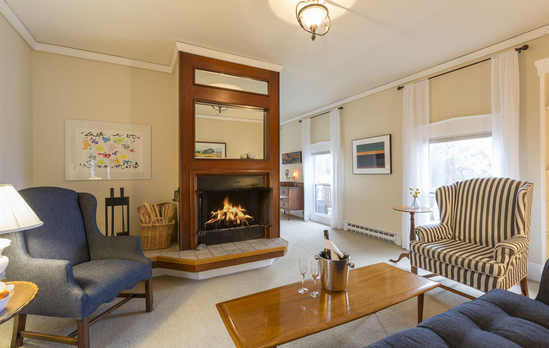 The Bayview Suite room with sitting area by a crackling fire.