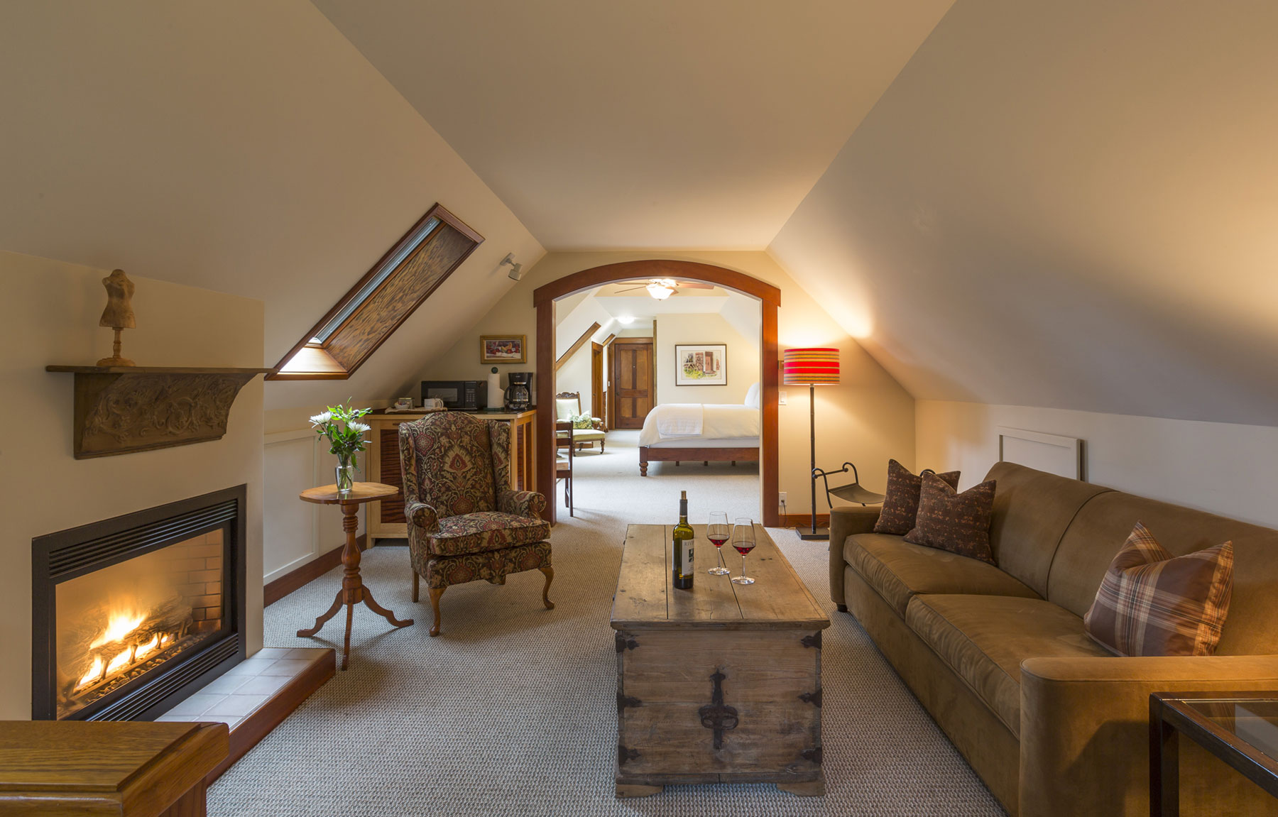 The Carriage House Grand Suite sitting room with eclectic furnishings and cozy fireplace