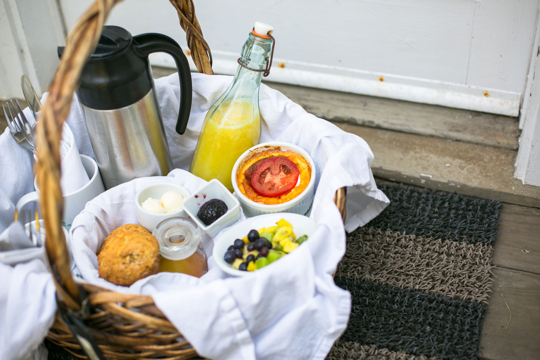 a basket of breakfast: egg soufflé, orange juice, muffins, cut fruit, and coffee