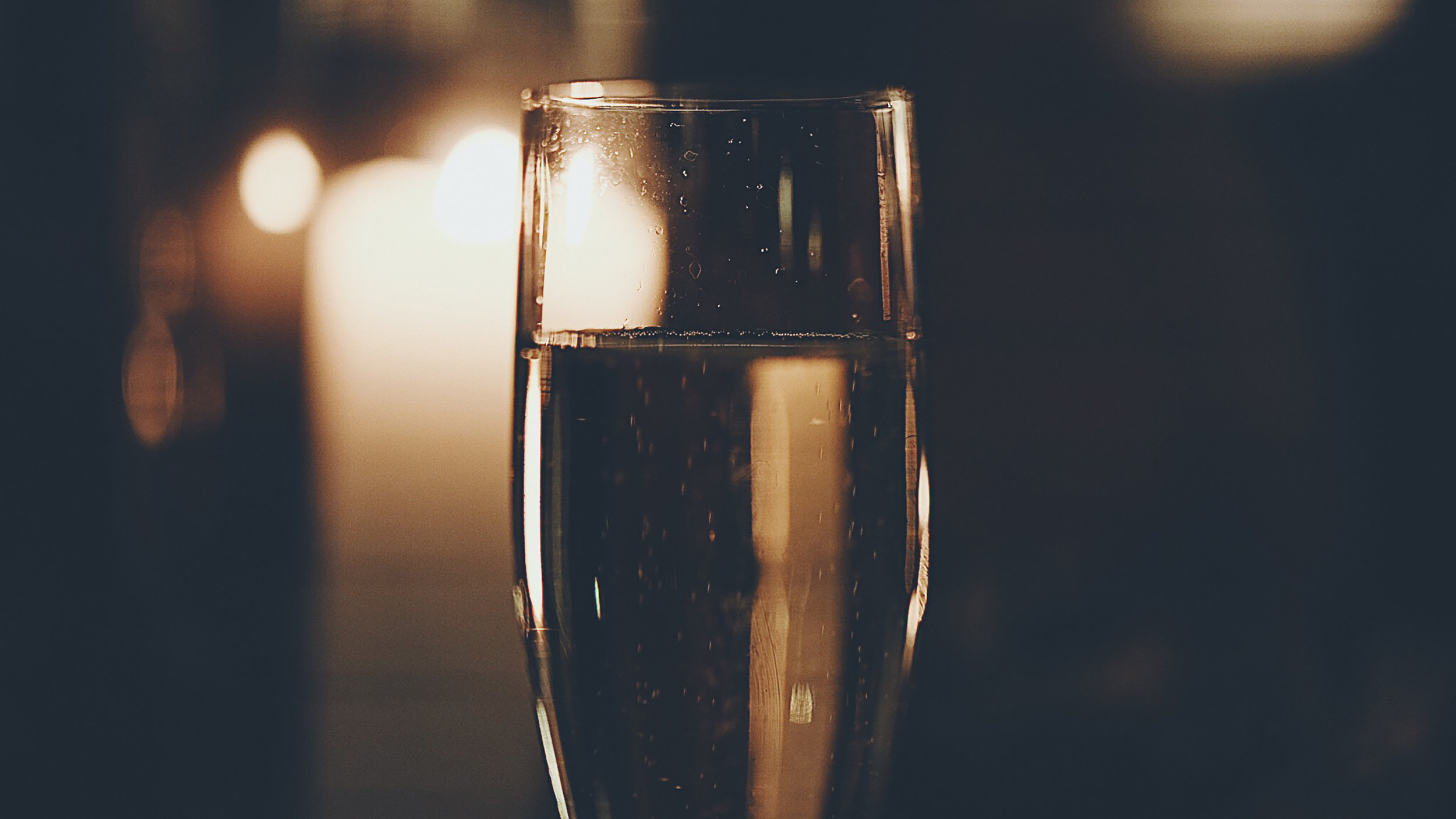 a glass of champagne with moody lighting