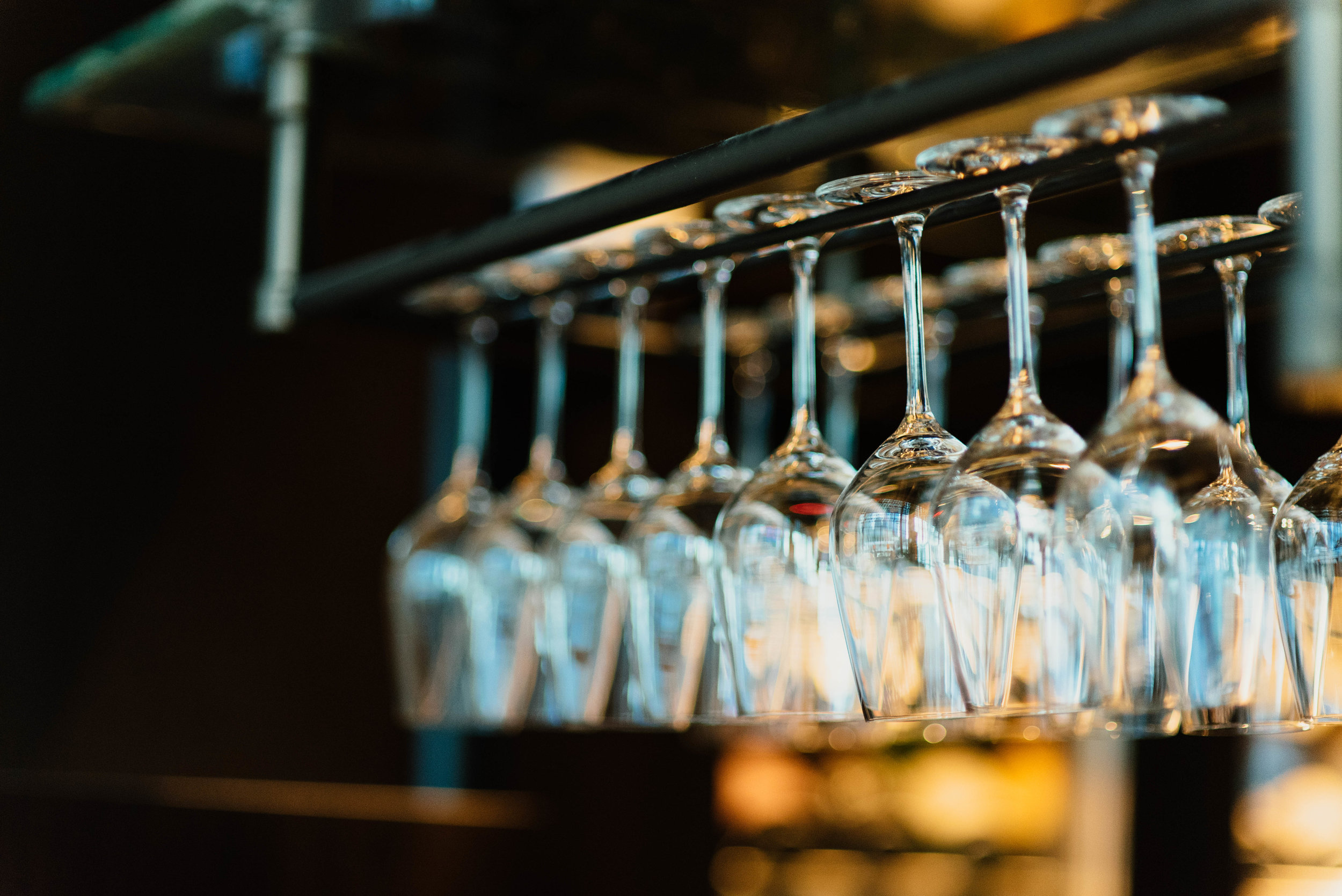 a collection of wine glasses hung upside down for easy reach