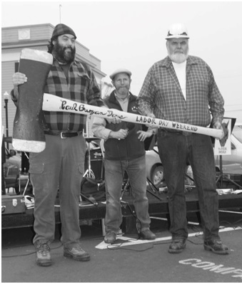 Three men dressed as lumberjacks holding an oversized axe
