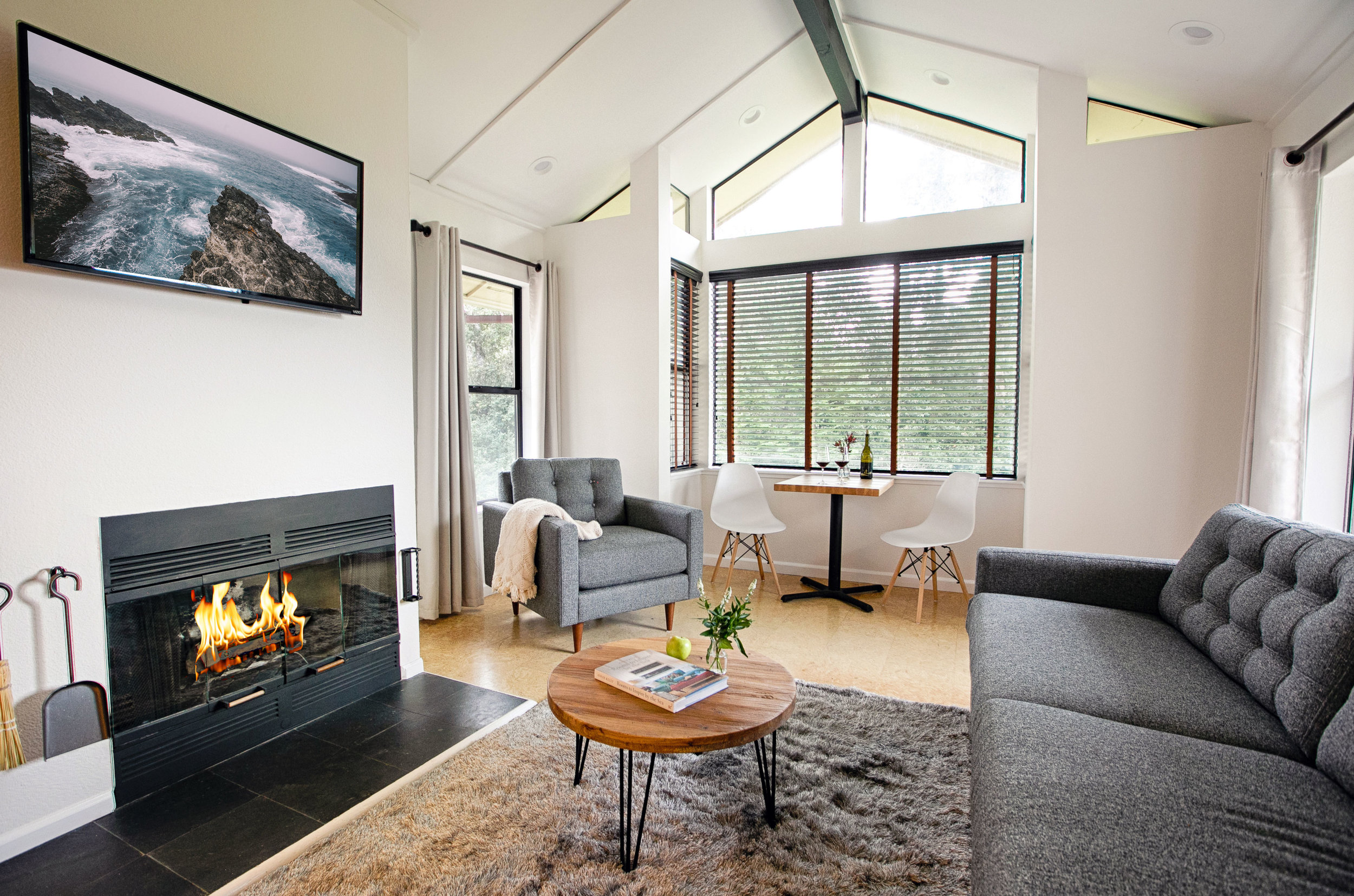 The sitting area in room 203 at The Lodge has modern furnishings with sofa, chair, and table with side chairs, as well as wood burning fire and flat screen TV.