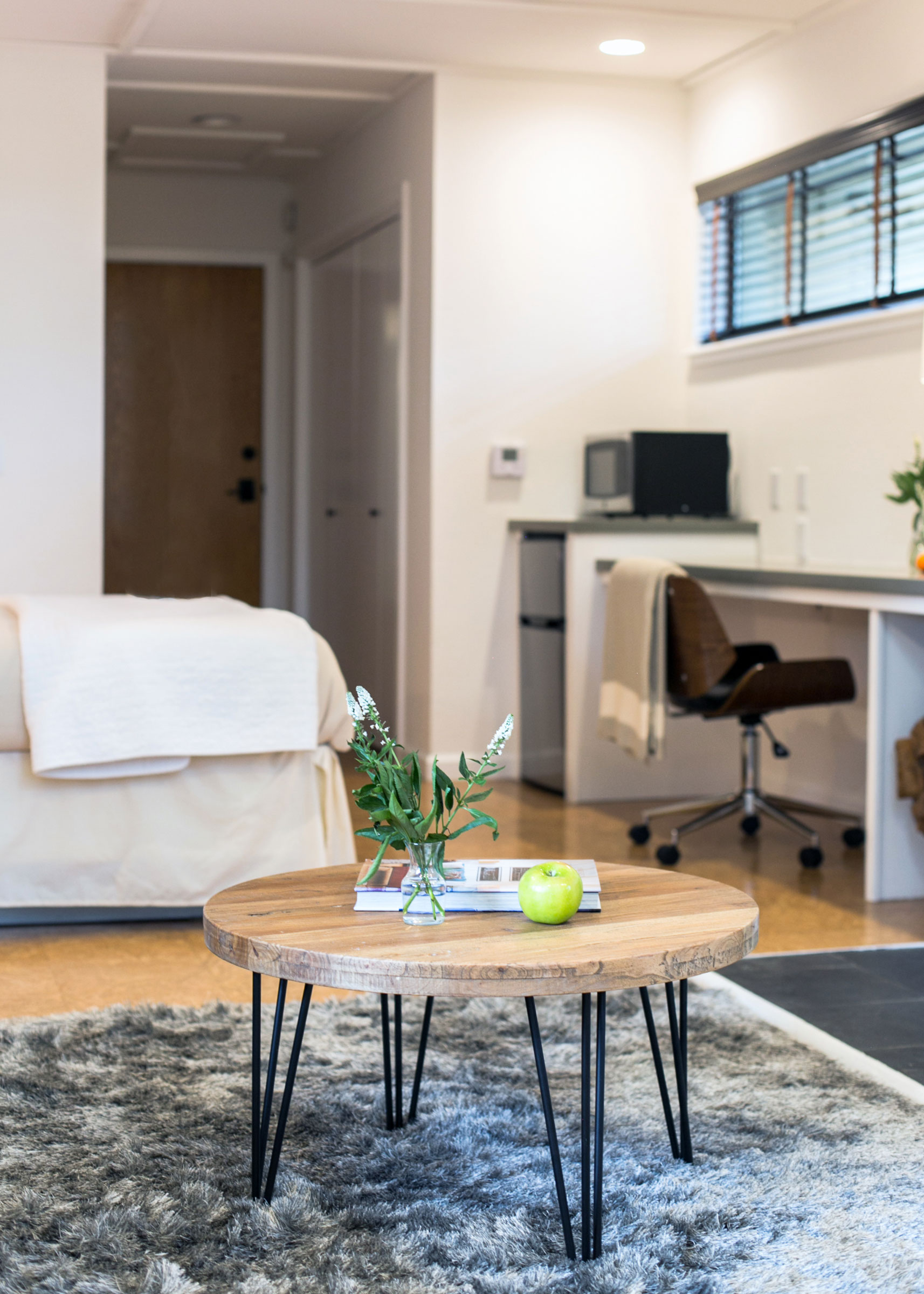 A modern coffee table sits on a plush grey rug in room 203 in the Lodge at Glendeven of Mendocino.