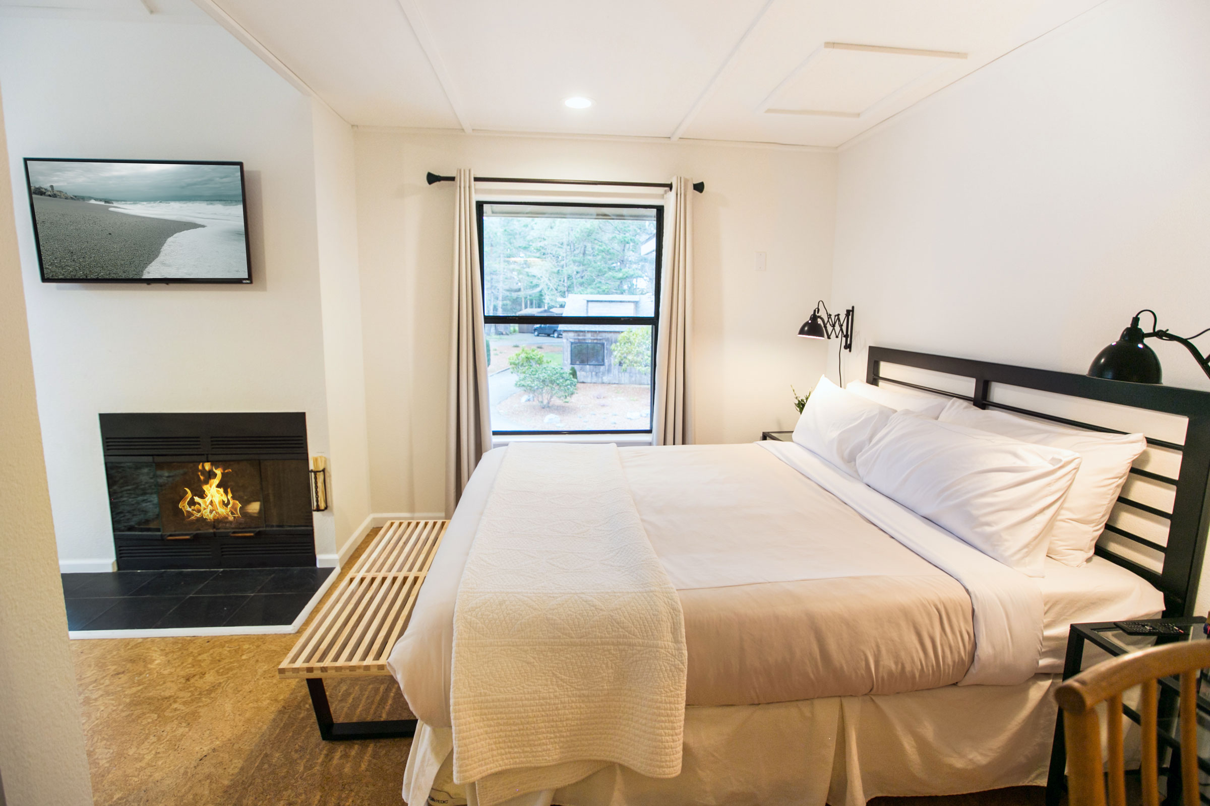 Room 202 in the Lodge at Glendeven with queen bed next to wood burning fireplace and flat screen TV.